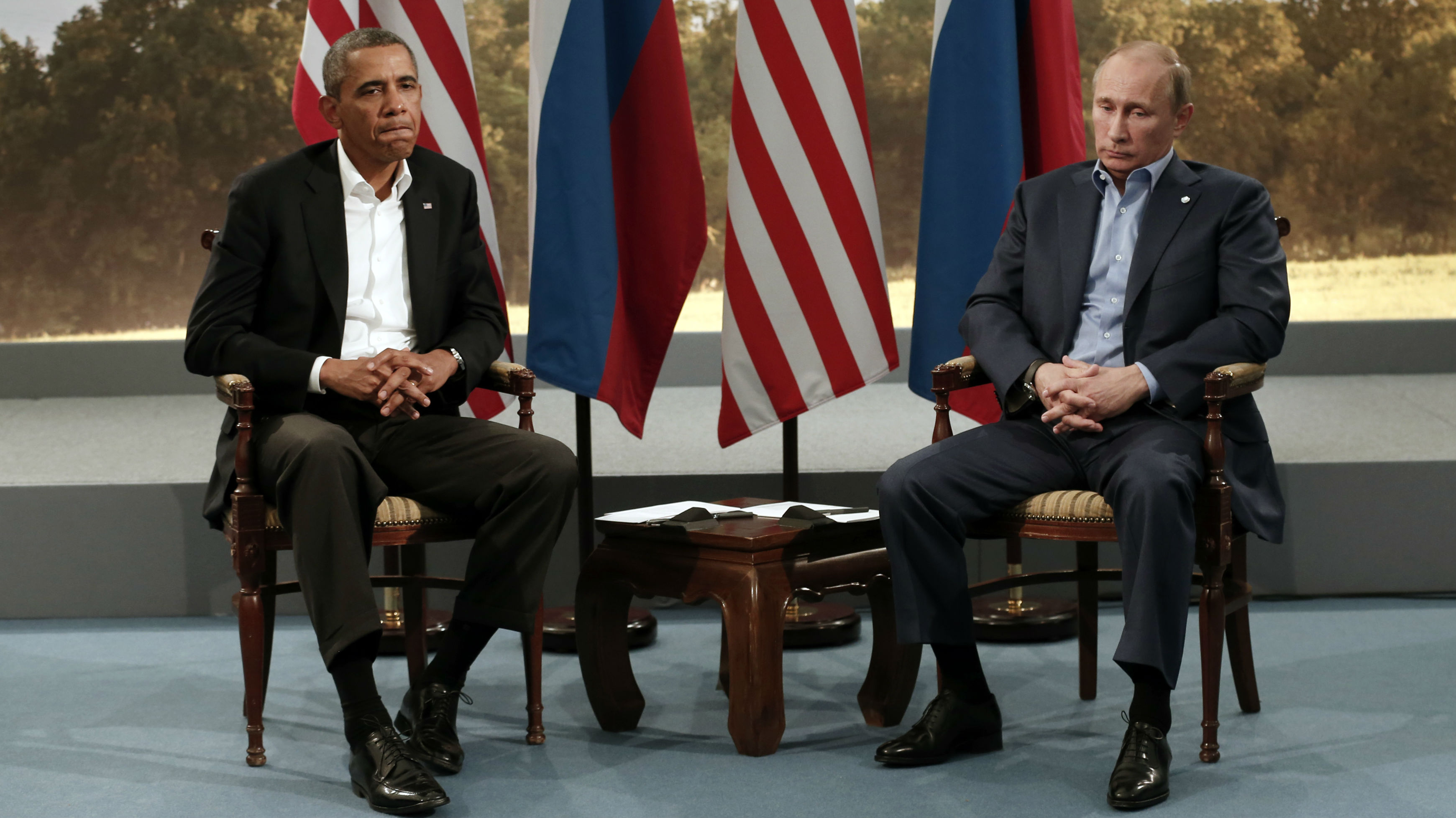 President Obama and President Putin sit in front of two American flags and two Russian flags.