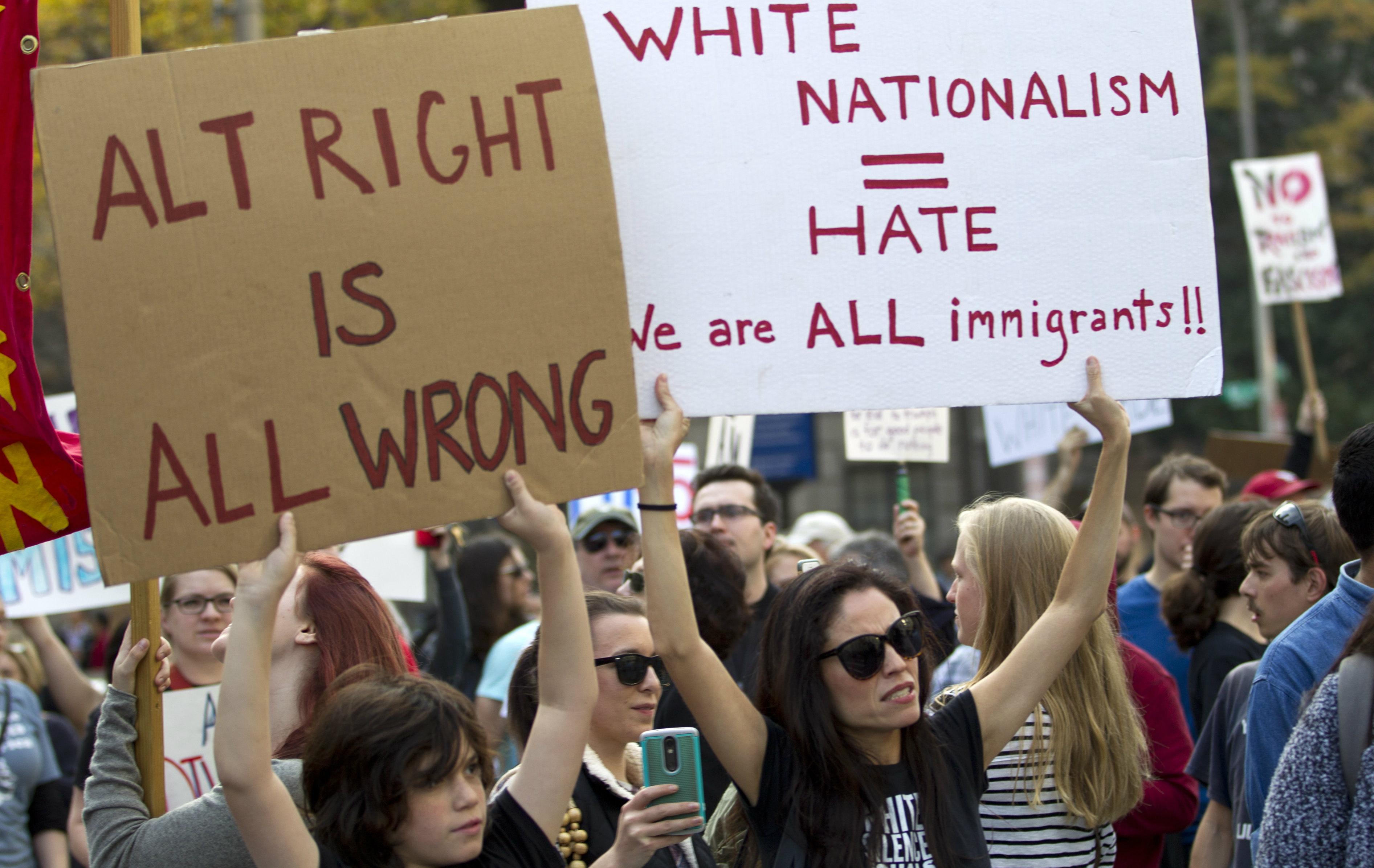 A woman and child holding up anti alt-right signs.