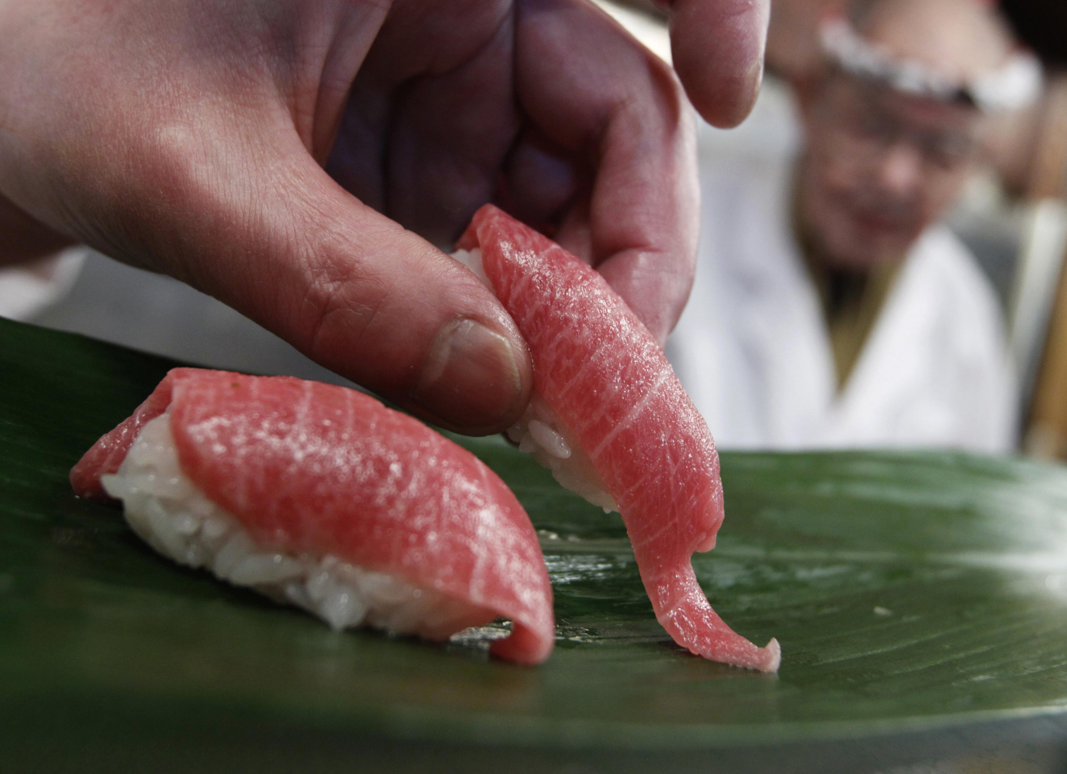 """A sushi chef serves sushi of high-quality fatty Atlantic bluefin tuna or """"o-toro sushi nigiri"""" at a sushi restaurant in Tokyo March 18, 2010."""
