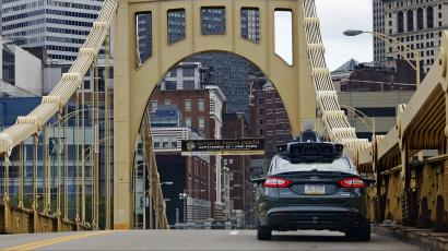 A self driving Uber car drives across the ninth street bridge in downtown Pittsburgh.