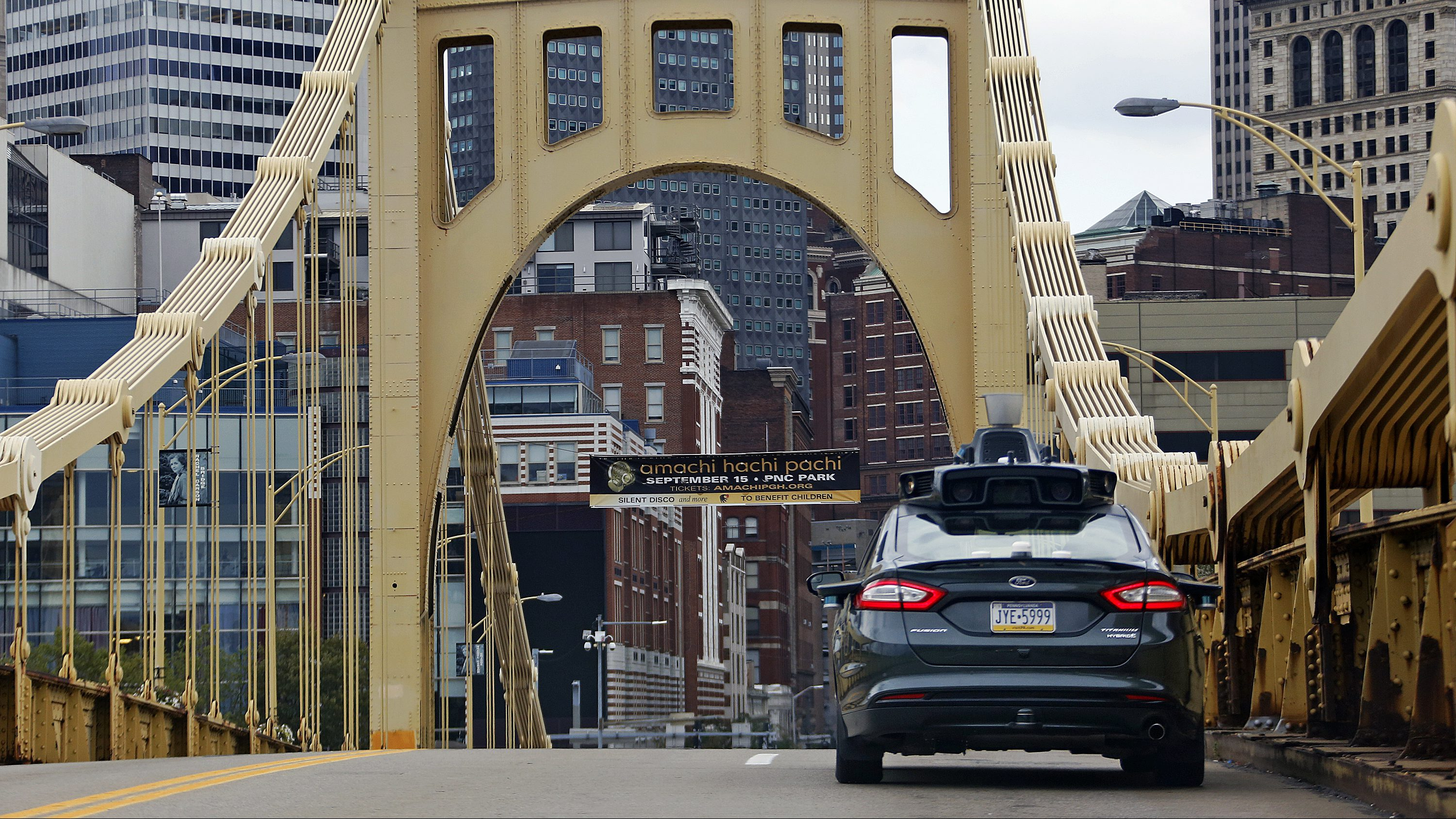 A self driving Uber car drives across the ninth street bridge in downtown Pittsburgh Wednesday, Sept. 14, 2016. On Wednesday, a fleet of self-driving Ford Fusions began picking up Uber riders who opted to participate in a test program. AP Photo/Gene J. Puskar)
