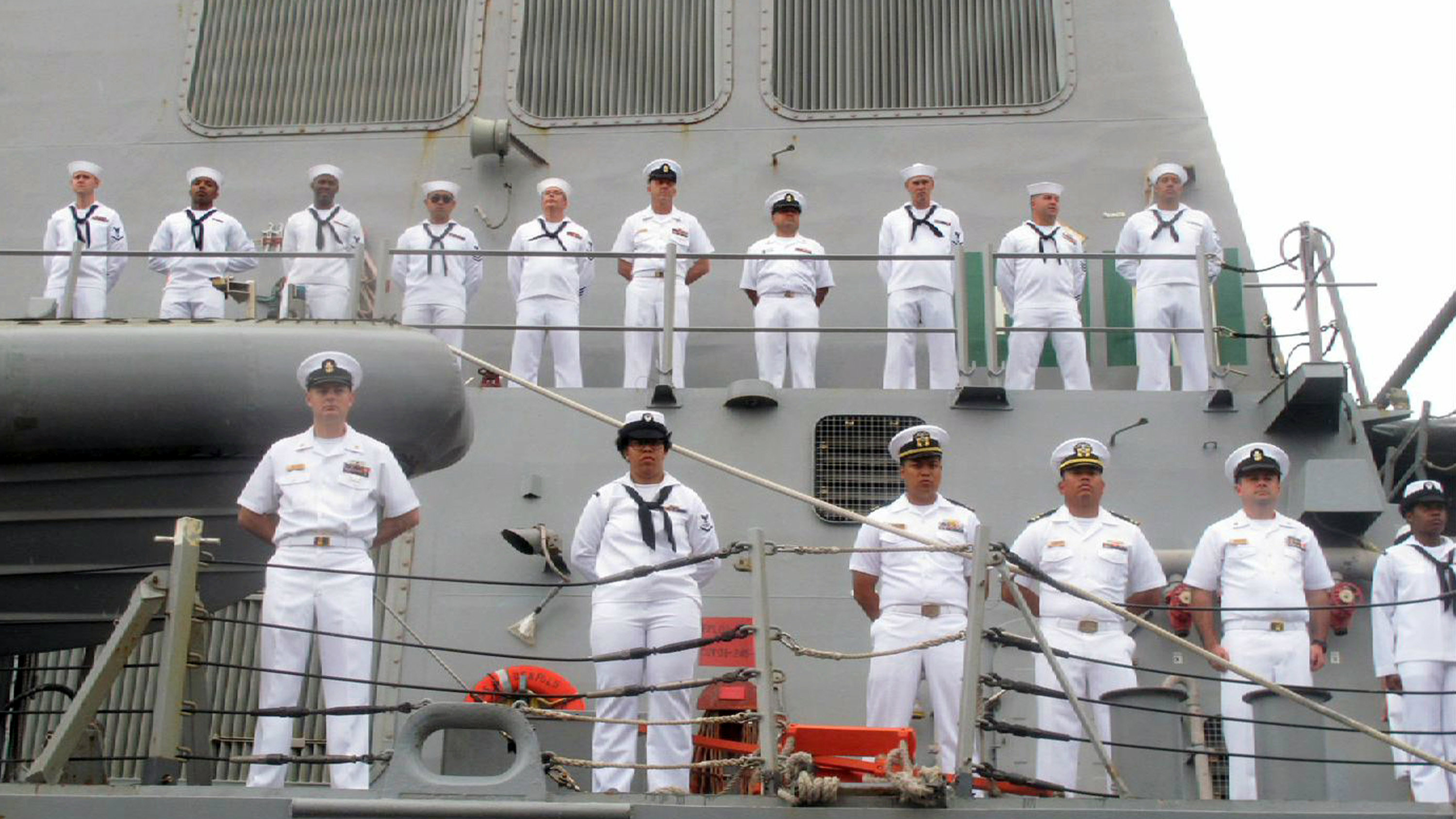 U.S. Navy sailors stand on deck as the guided missile destroyer USS Benfold arrives in port in Qingdao in eastern China's Shandong Province.