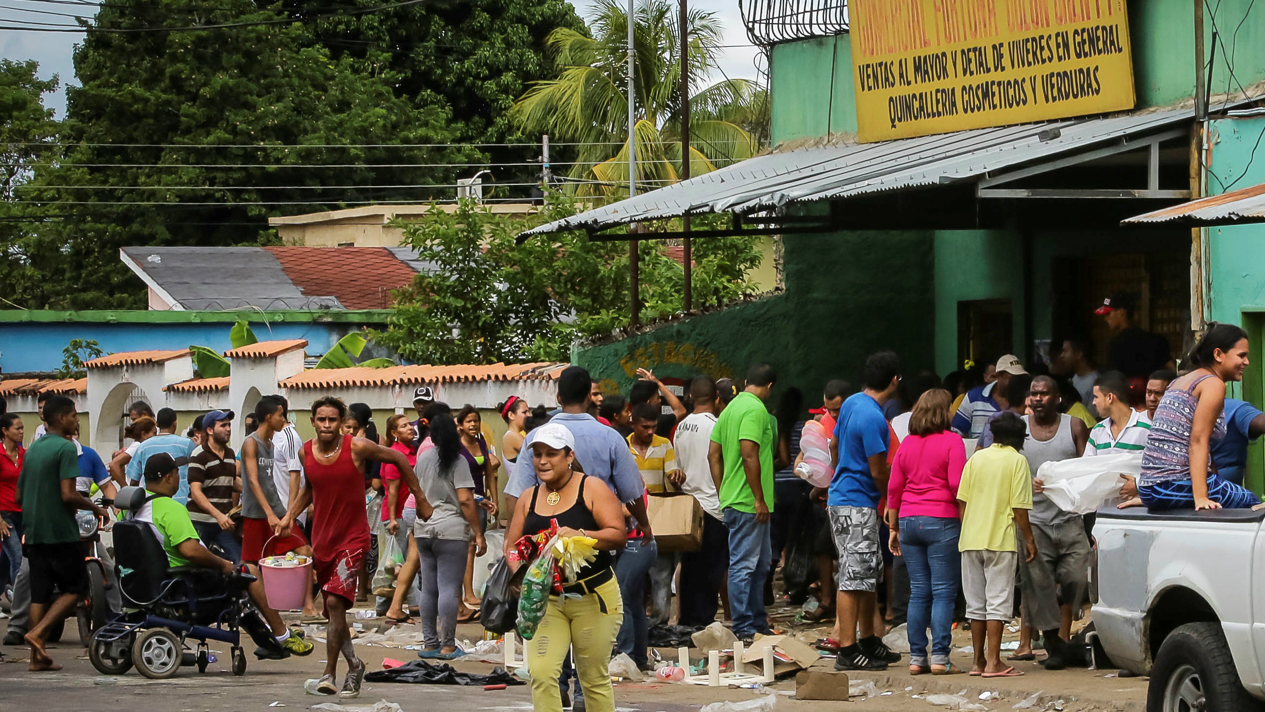 People take food from a looted shop in Venezuela.