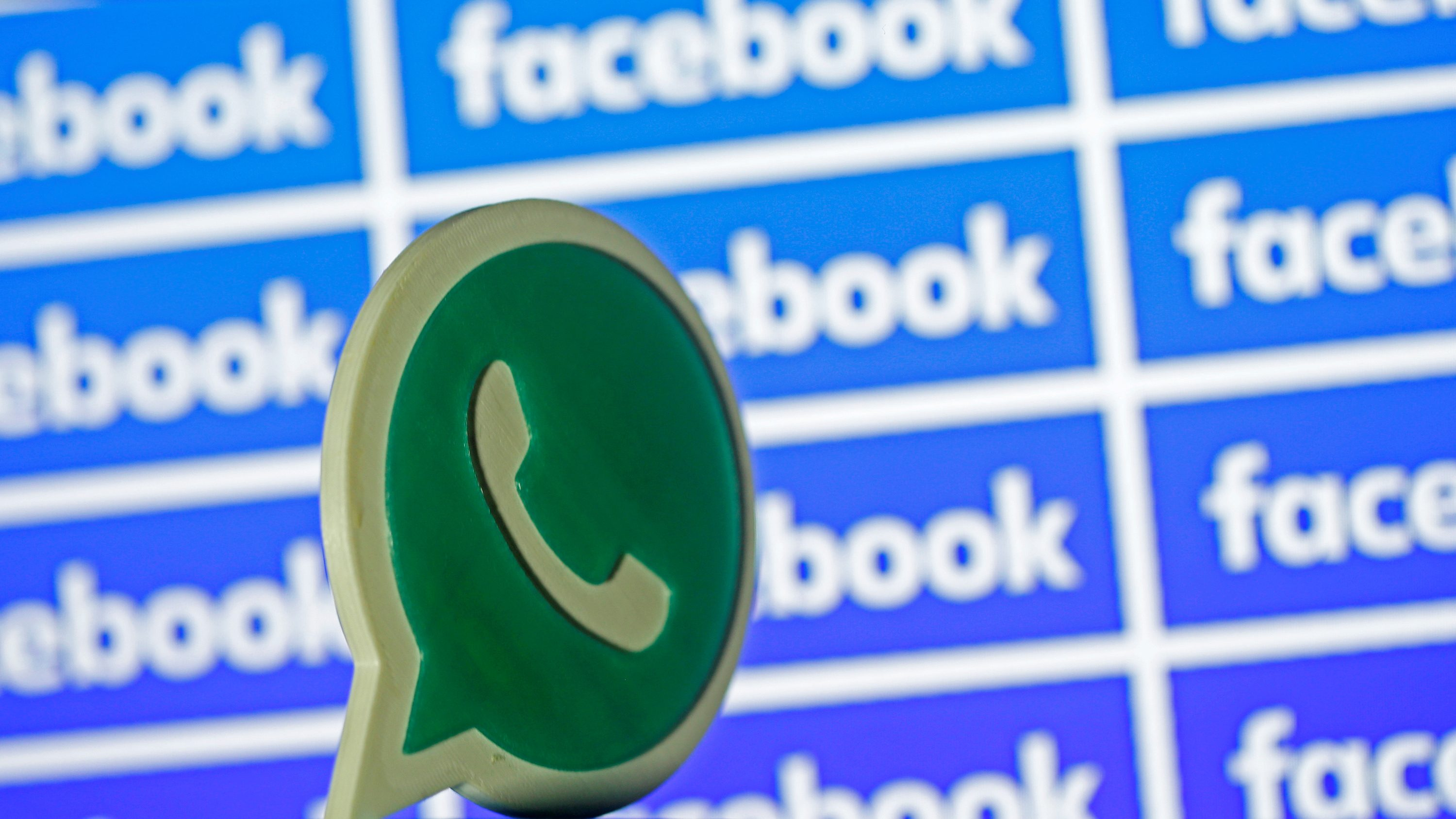 A 3D printed Whatsapp  logo is seen in front of a displayed Facebook logo in this illustration taken April 28, 2016.