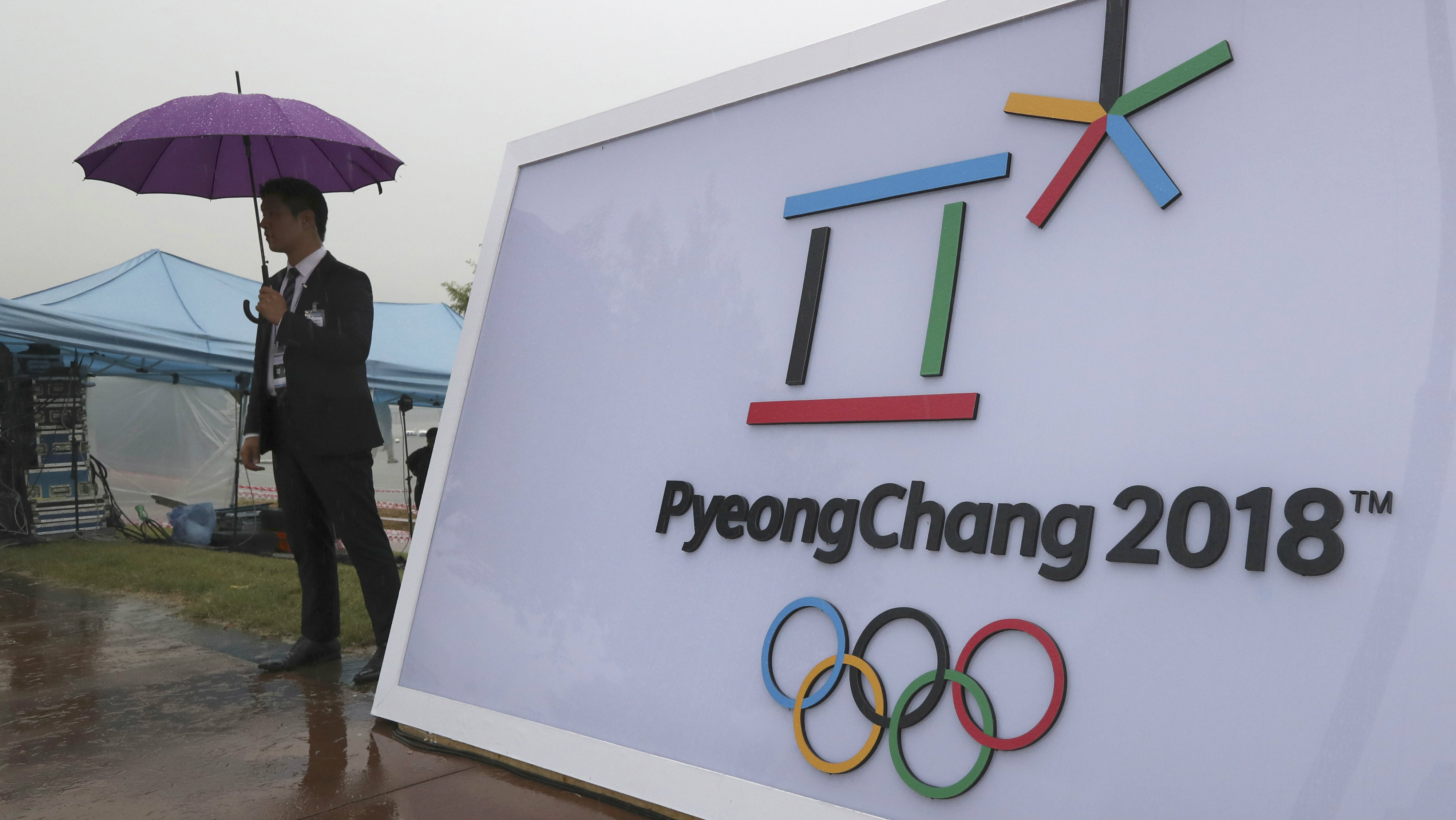 Security personnel stands by a logo of the 2018 PyeongChang Olympic Winter Games before an event to mark the start of the 500-day countdown in Seoul, South Korea, Tuesday, Sept. 27, 2016.