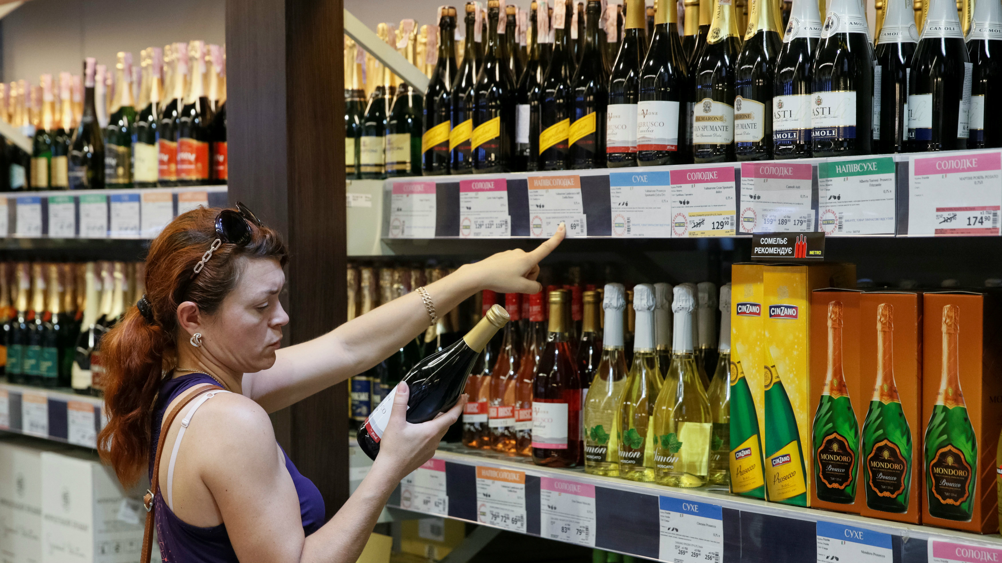 A woman buys a bottle of wine at a Metro cash and carry store in Kiev, Ukraine, August 17, 2016. REUTERS/Valentyn Ogirenko