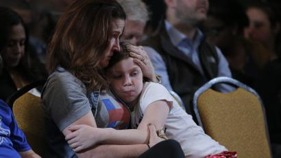 A member of the campaign staff of former Democratic U.S. presidential candidate Hillary Clinton hugs her young daughter as they wait for Clinton to appear and speak after losing the election to U.S. President-elect Donald Trump, at a hotel in the Manhattan borough of New York, U.S., November 9, 2016. REUTERS/Brian Snyder - RTX2SUVL