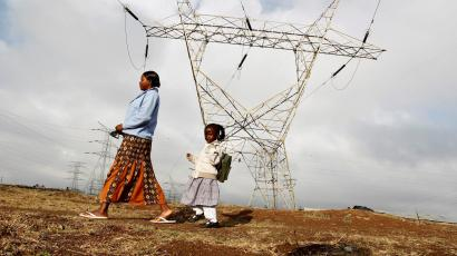 A woman walks her child to school past high voltage electrical pylons on the outskirts of Kenya's capital Nairobi,