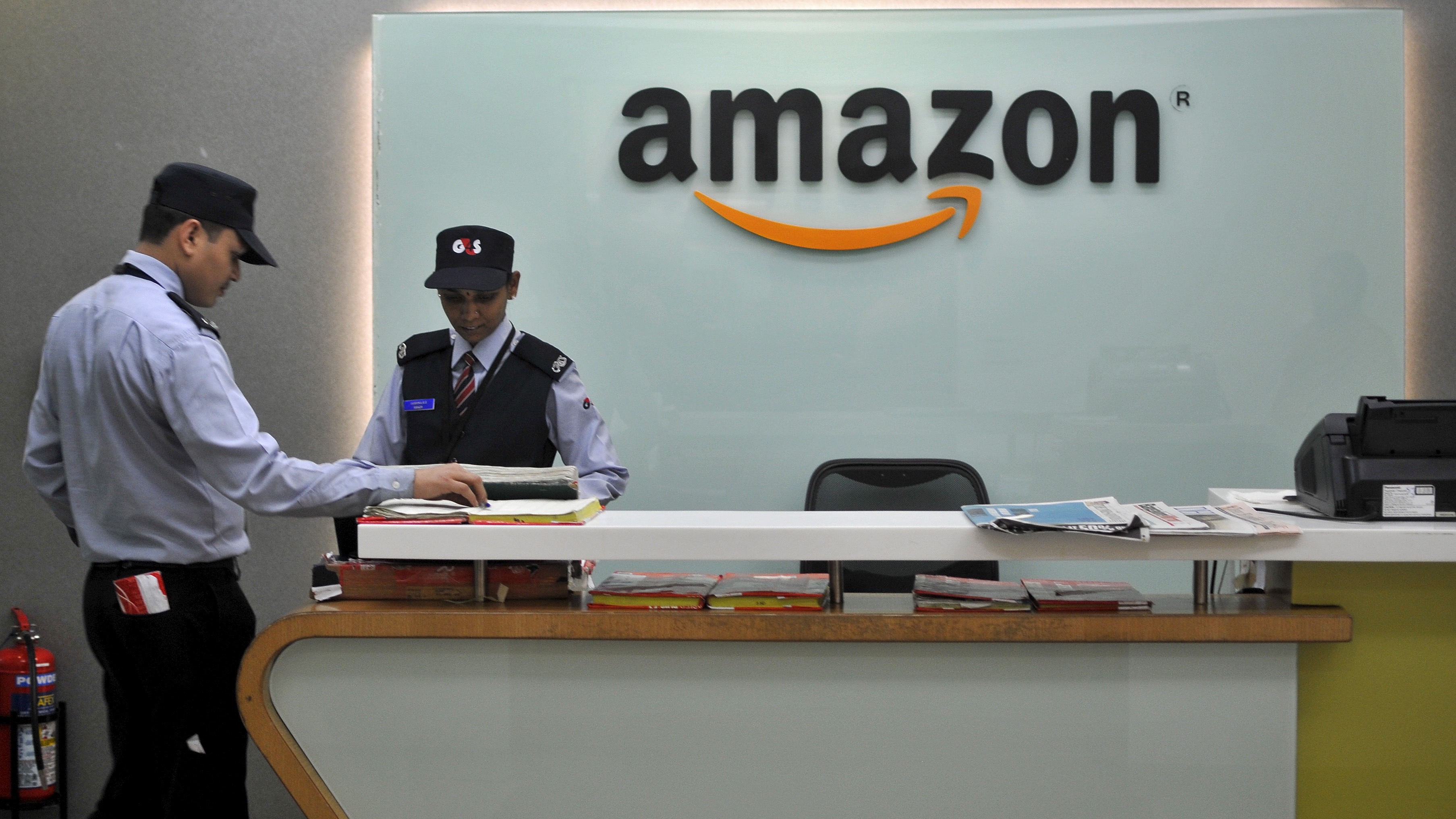 Security guards stand at the reception desk of the Amazon India office in Bengaluru, India, August 14, 2015. E-commerce giant Amazon.com is taking lessons learnt from its daily battles with India's choked roads and cramped cities to some of its largest developed markets, exporting a model of cheaper deliveries and reduced warehousing costs. Picture taken August 14, 2015. To match AMAZON.COM-INDIA/LOGISTICS REUTERS/Abhishek N. Chinnappa - RTS6Q3P