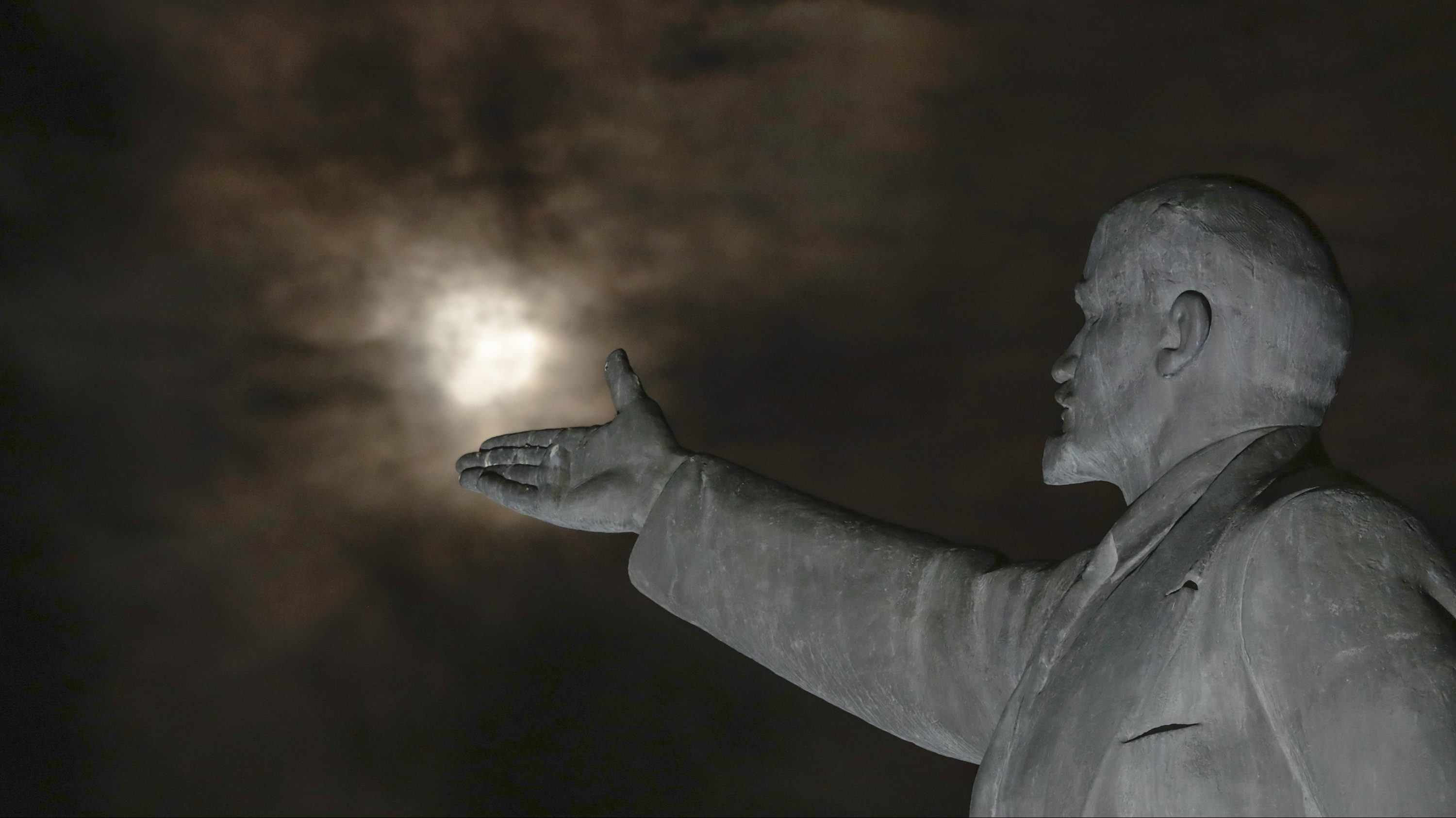 The super moon rises through the clouds over a statue of Soviet Union founder Vladimir Lenin at the Russian leased Baikonur cosmodrome, Kazakhstan, Monday, Nov. 14, 2016.