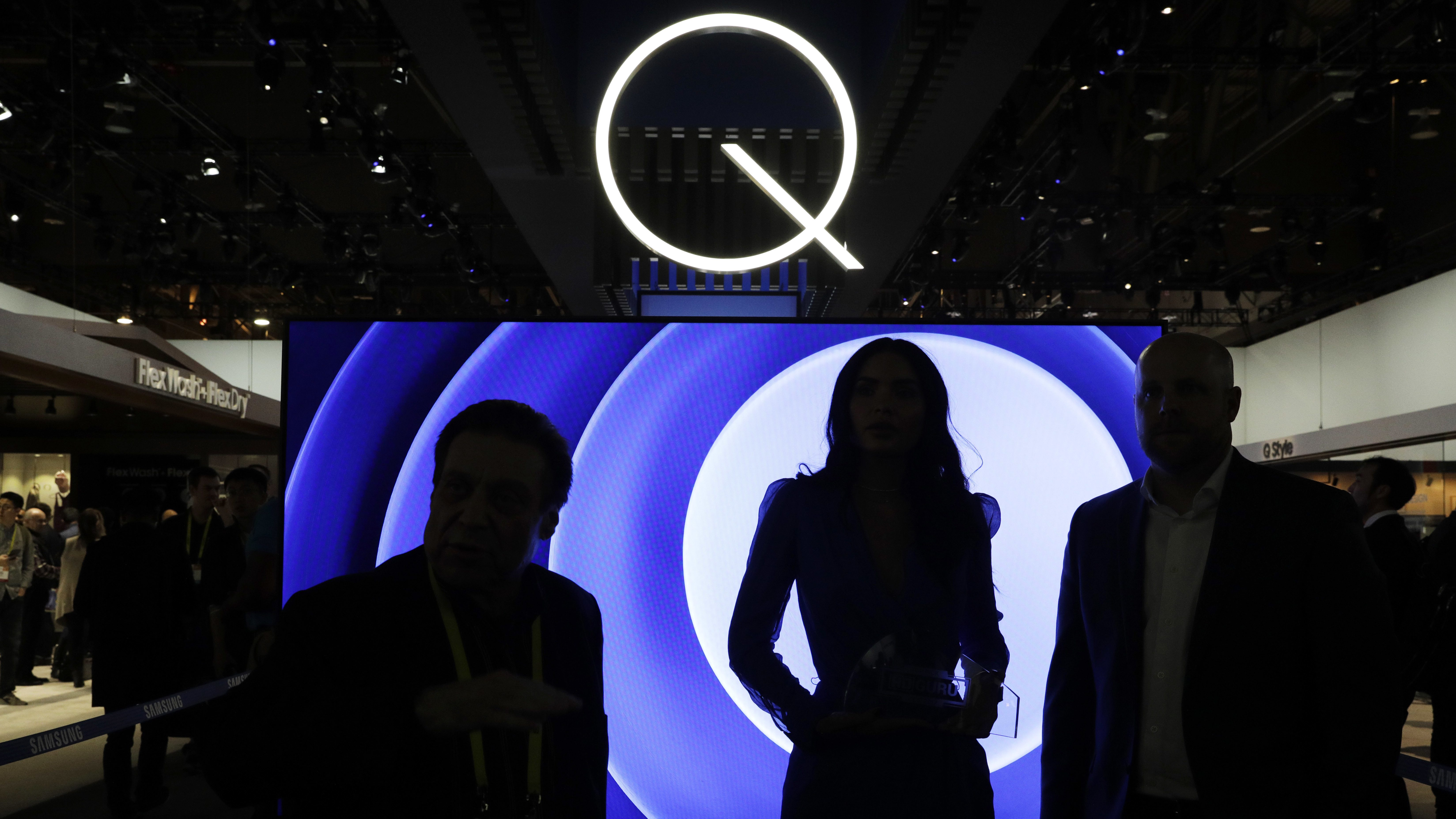 Attendees stand in front of a QLED TV at the Samsung booth during CES International, Friday, Jan. 6, 2017, in Las Vegas. (AP Photo/John Locher)