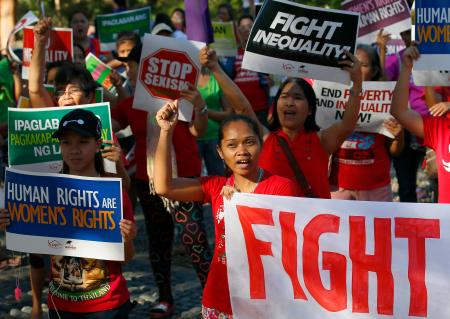 "Women shout slogans with placards during a rally in solidarity against the inauguration of President Donald Trump, Saturday, Jan. 21, 2017 in suburban Quezon city, northeast of Manila, Philippines. Pledging emphatically to empower America's ""forgotten men and women,"" Donald Trump was sworn in as President of the United States Friday, taking command of a riven nation facing an unpredictable era under his assertive but untested leadership."