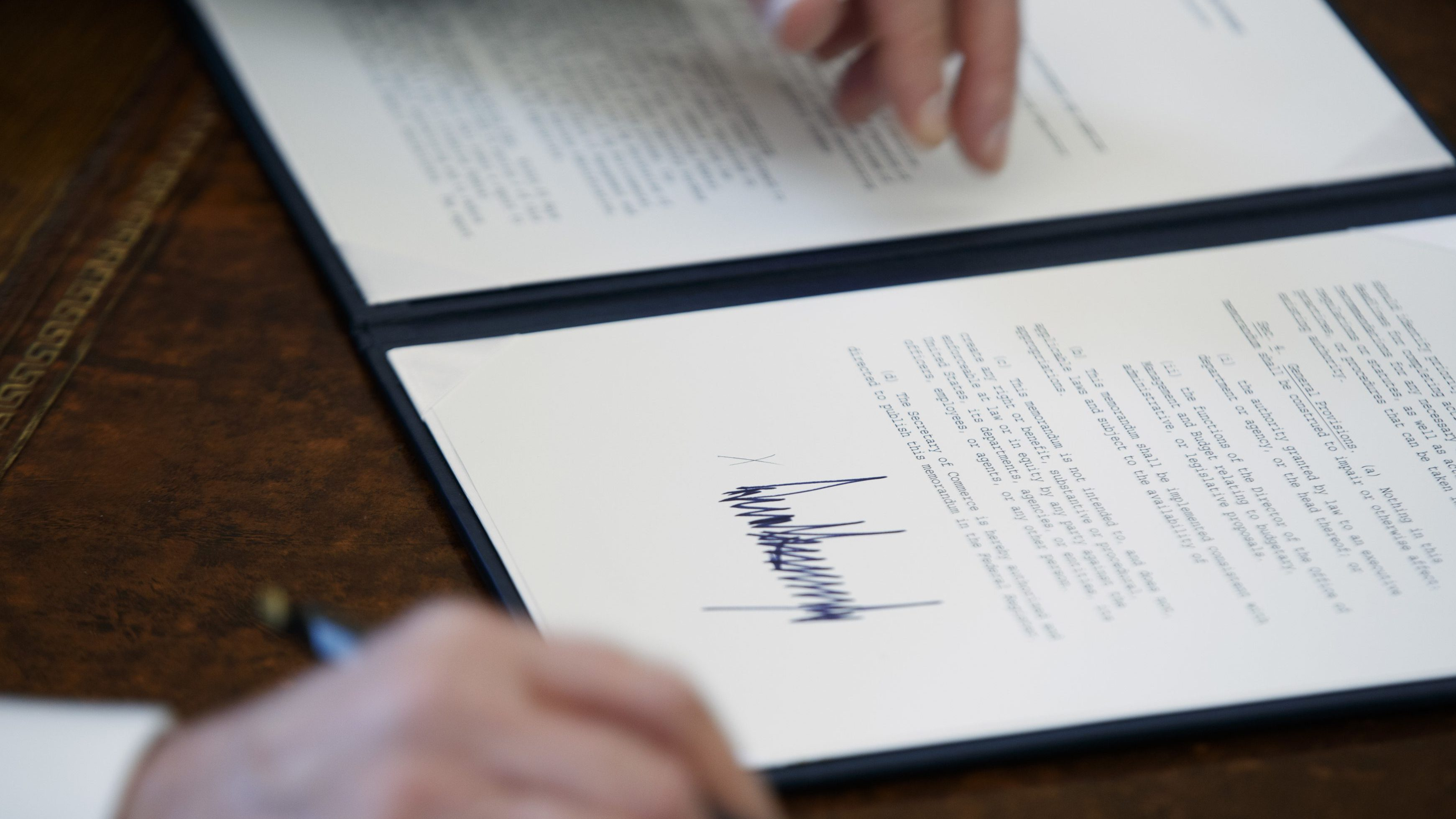 The signature of President Donald Trump is seen on an executive order in Oval Office of the White House.