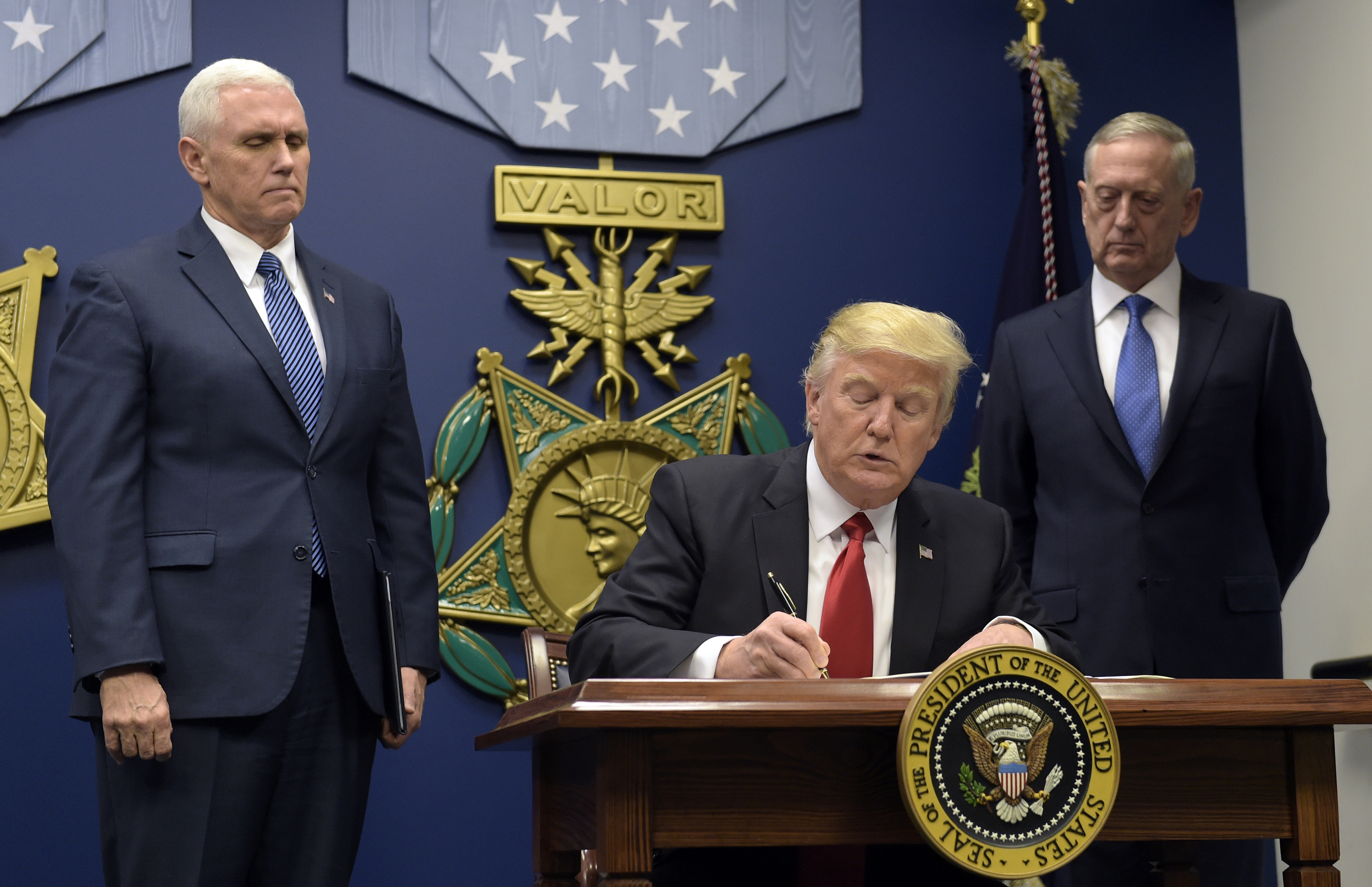 President Donald Trump, center, with Vice President Mike Pence, left, and Defense Secretary James Mattis, right, watching, signs an executive action on extreme vetting at the Pentagon in Washington, Friday, Jan. 27, 2017. (AP Photo/Susan Walsh)