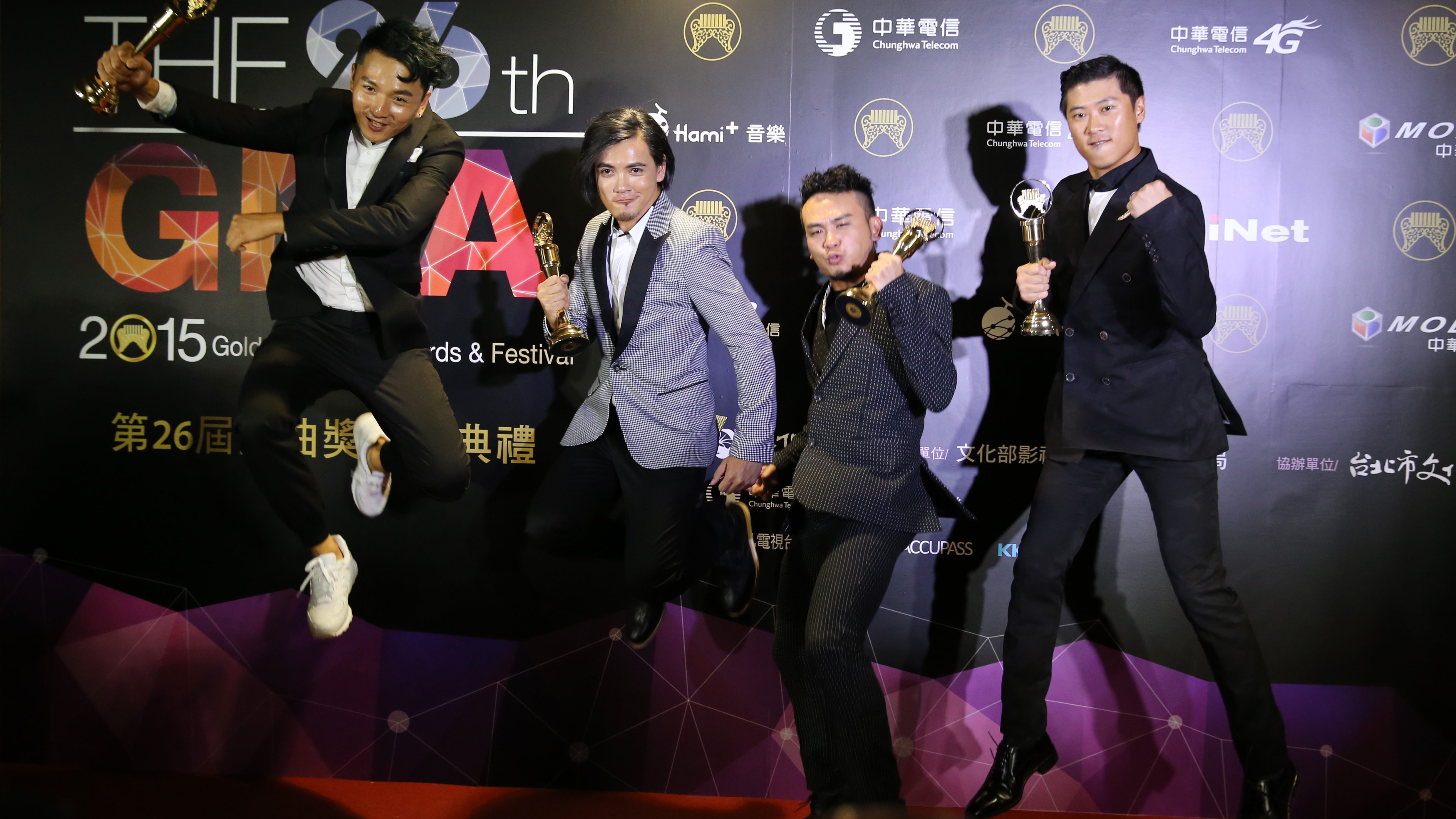Taiwanese pop group Fire EX. jumps in the air for media as they display their awards for the Best Song at the 26th Golden Melody Awards in Taipei, Taiwan, Saturday, June 27, 2015. Fire EX. is nominated as the Best Song at this year's Golden Melody Awards, one of the world's biggest Chinese-language pop music annual events. (AP Photo/Wally Santana)