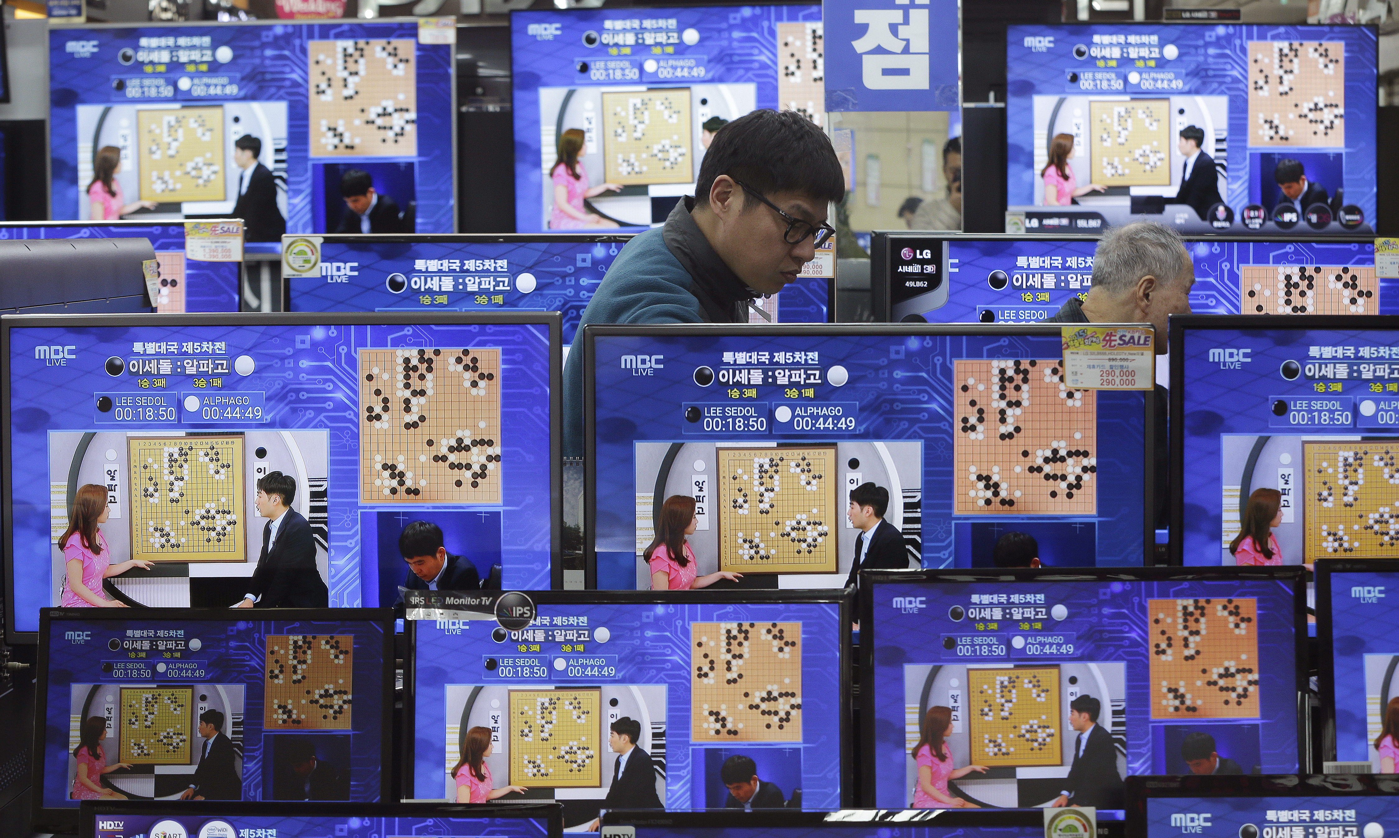 TV screens show the live broadcast of the Google DeepMind Challenge Match between Google's artificial intelligence program, AlphaGo, and South Korean professional Go player Lee Sedol, at the Yongsan Electronic store in Seoul, South Korea, Tuesday, March 15, 2016. Google's Go-playing computer program again defeated its human opponent in a final match on Tuesday sealing its 4:1 victory.