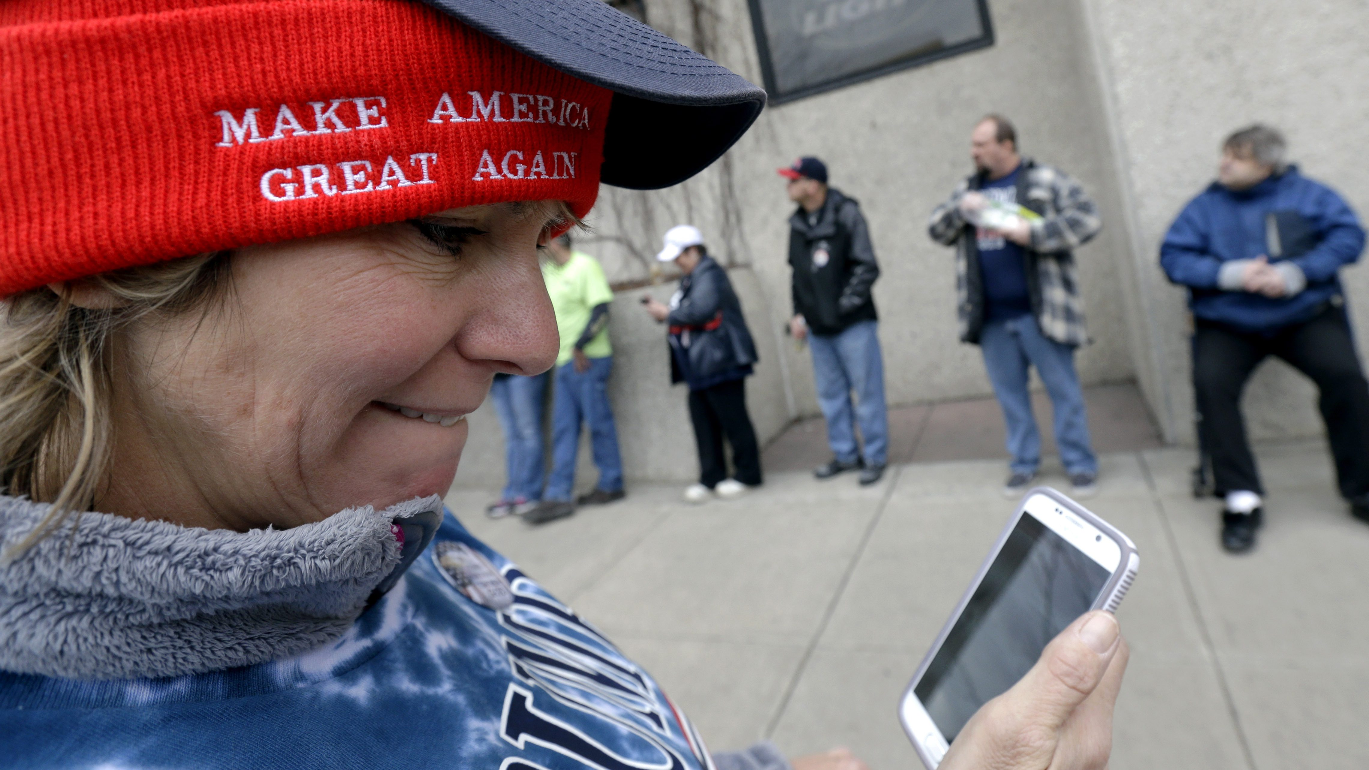 Lori Levis checks her phone outside the Radisson Paper Valley Hotel in Appleton, Wis., Wednesday, March 30, 2016, where Republican presidential candidate Donald Trump is scheduled to appear for a rally. (AP Photo/Nam Y. Huh)
