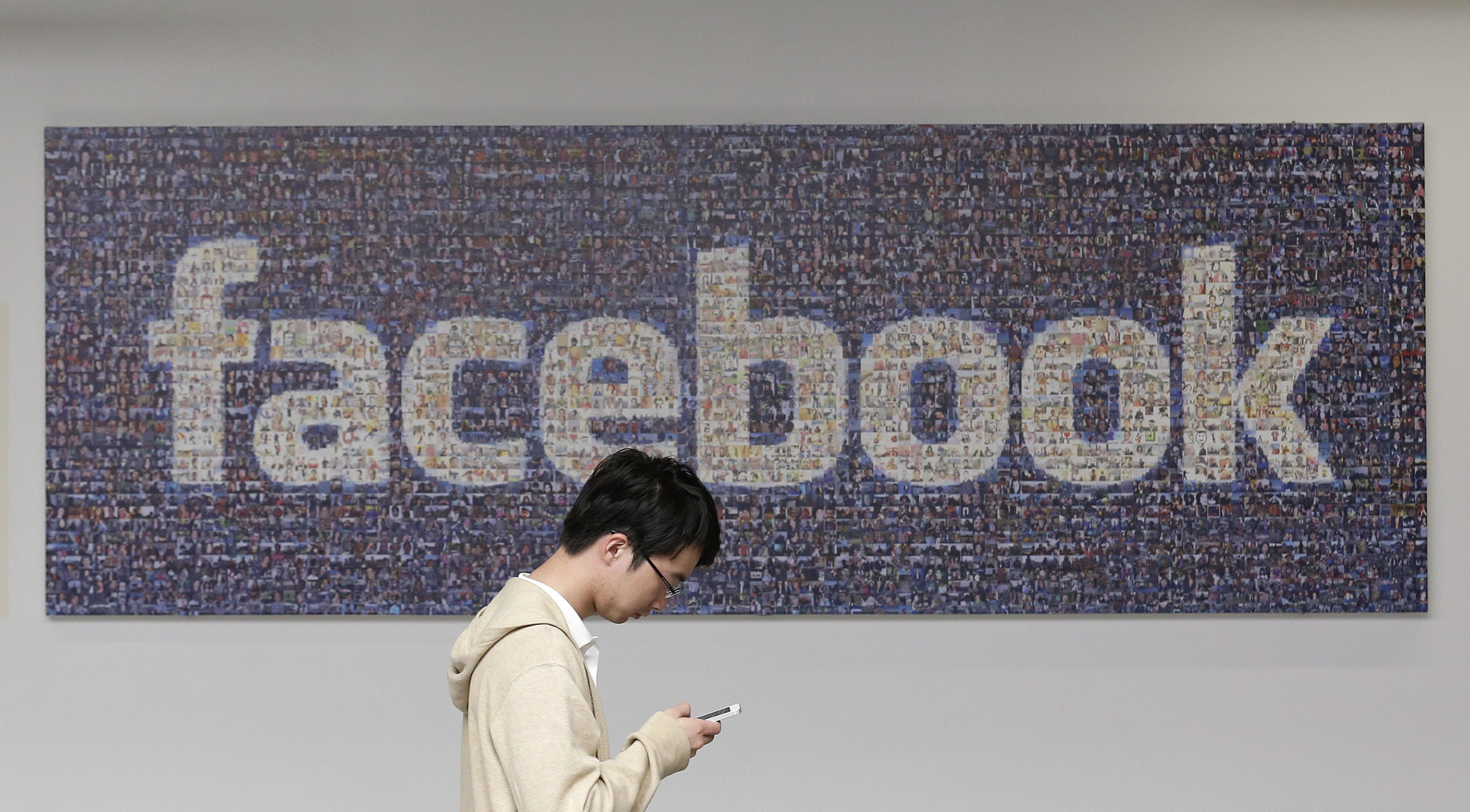 In this June 11, 2014 photo, a man walks past a Facebook sign in an office on the Facebook campus in Menlo Park, Calif. The Proceedings of the National Academy of Sciences says that as a private company, Facebook had no obligation to adhere to rules on the use of human subjects in the study. But the journal says Facebook's data collection practices may have violated scientific principles requiring the consent of study subjects.