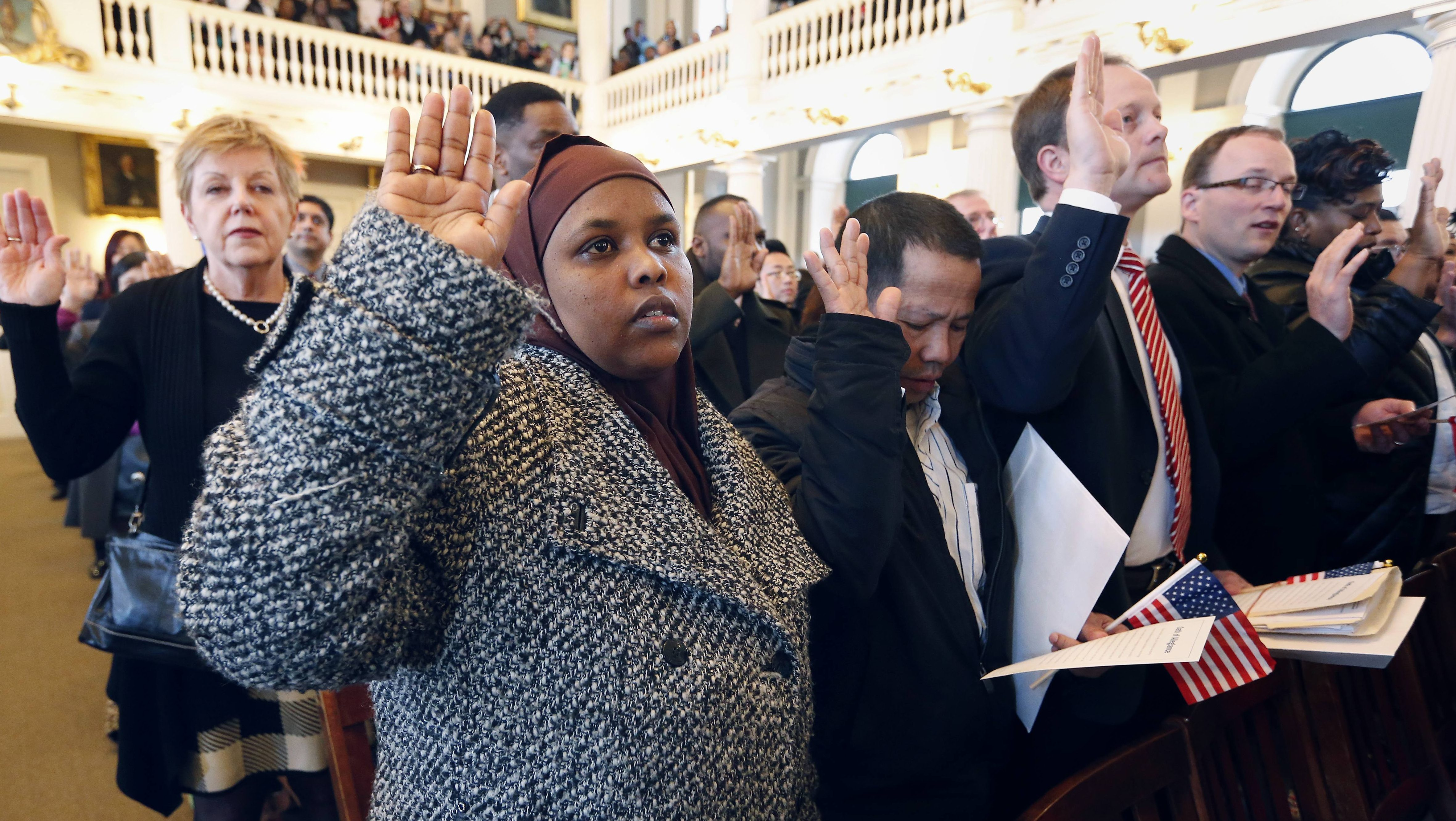 Hawd Ahmed, front left, who came from Somalia, takes the oath of U.S. citizenship during a naturalization ceremony in Boston, Thursday, April 2, 2015. Nearly 400 people from dozens of countries ranging from Albania to Zimbabwe took part in the ceremony.