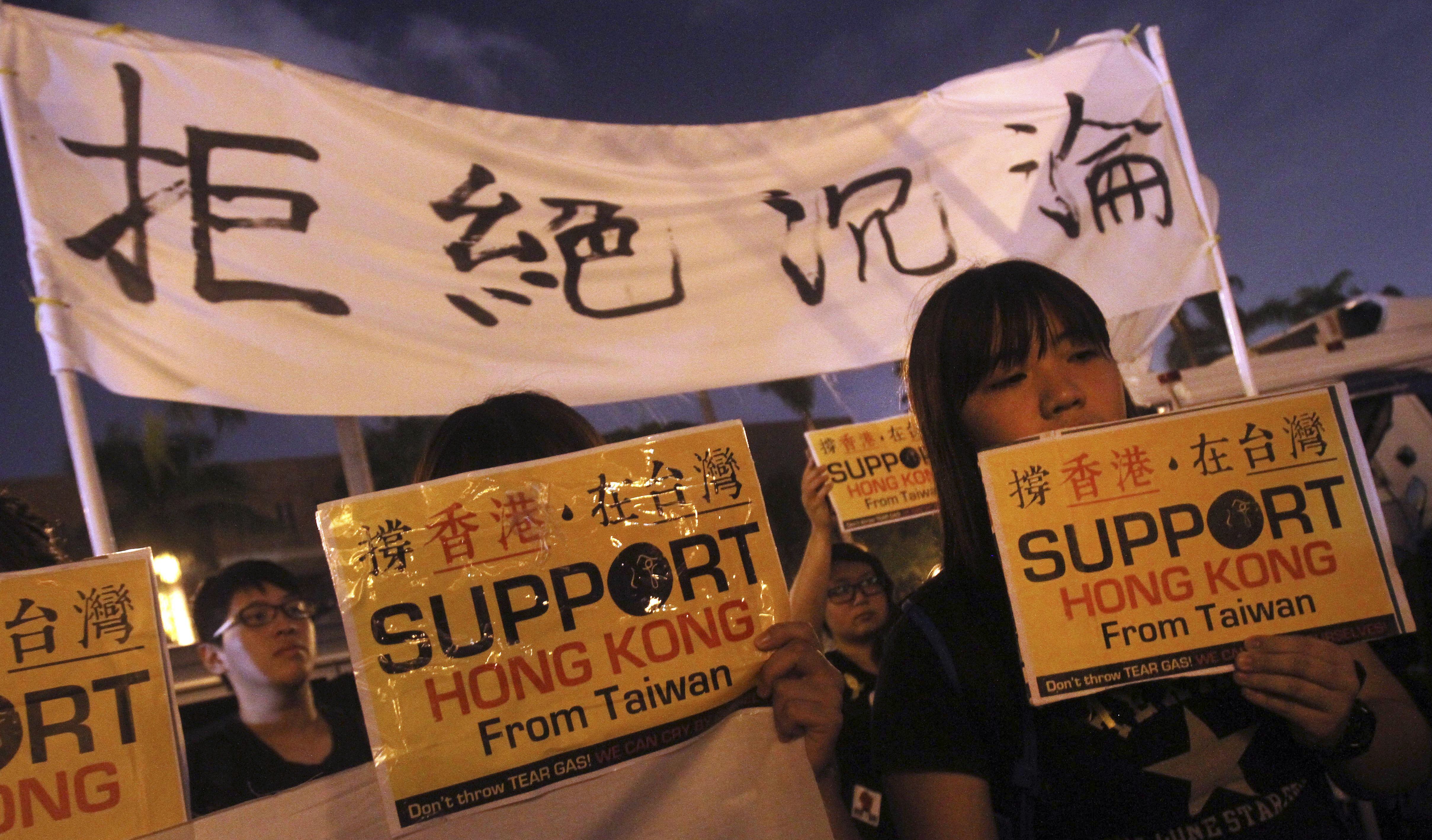 Demonstrators gather and hold slogans to support pro-democracy protests taking place in Hong Kong at Liberty Square in Taipei, Taiwan, Oct. 1, 2014.