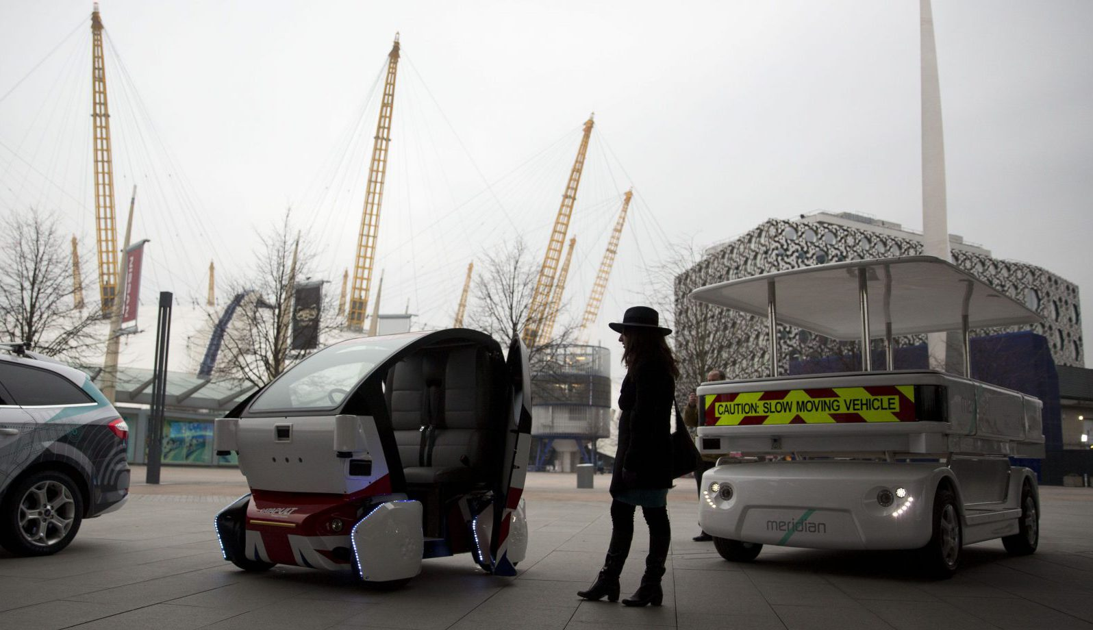 A woman poses for photographers beside a prototype driverless car called a LUTZ (Low-carbon Urban Transport Zone) Pathfinder Pod, center, and a Meridian shuttle, right, during a launch event for the media near the O2 Arena in London