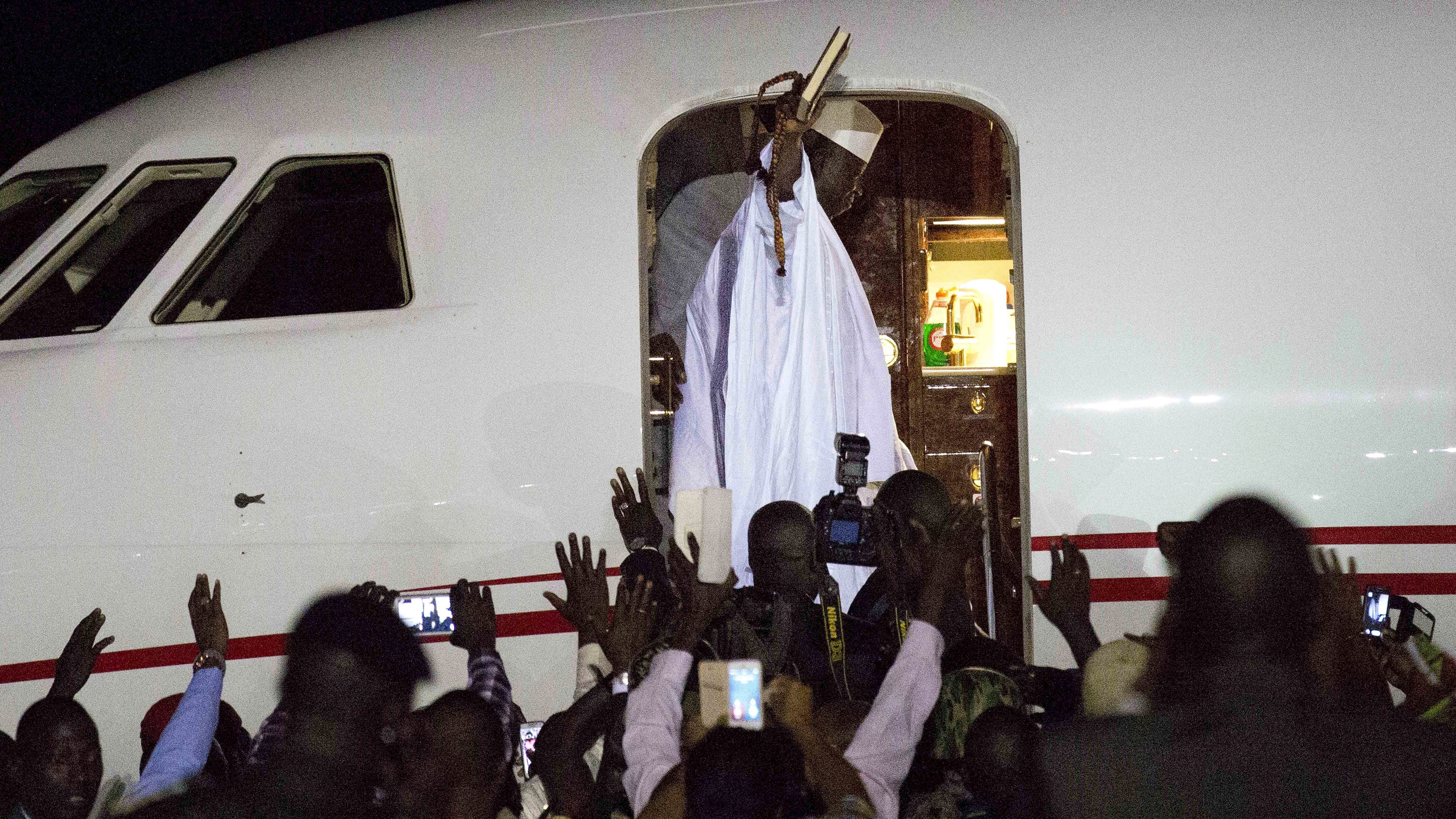 Gambia's defeated leader Yahya Jammeh waves to supporters as he departs from Banjul airport Saturday Jan. 21, 2017.  Jammeh announced early Saturday he has decided to relinquish power, after hours of last-ditch talks with regional leaders and the threat by a regional military force to make him leave. (AP Photo/Jerome Delay)