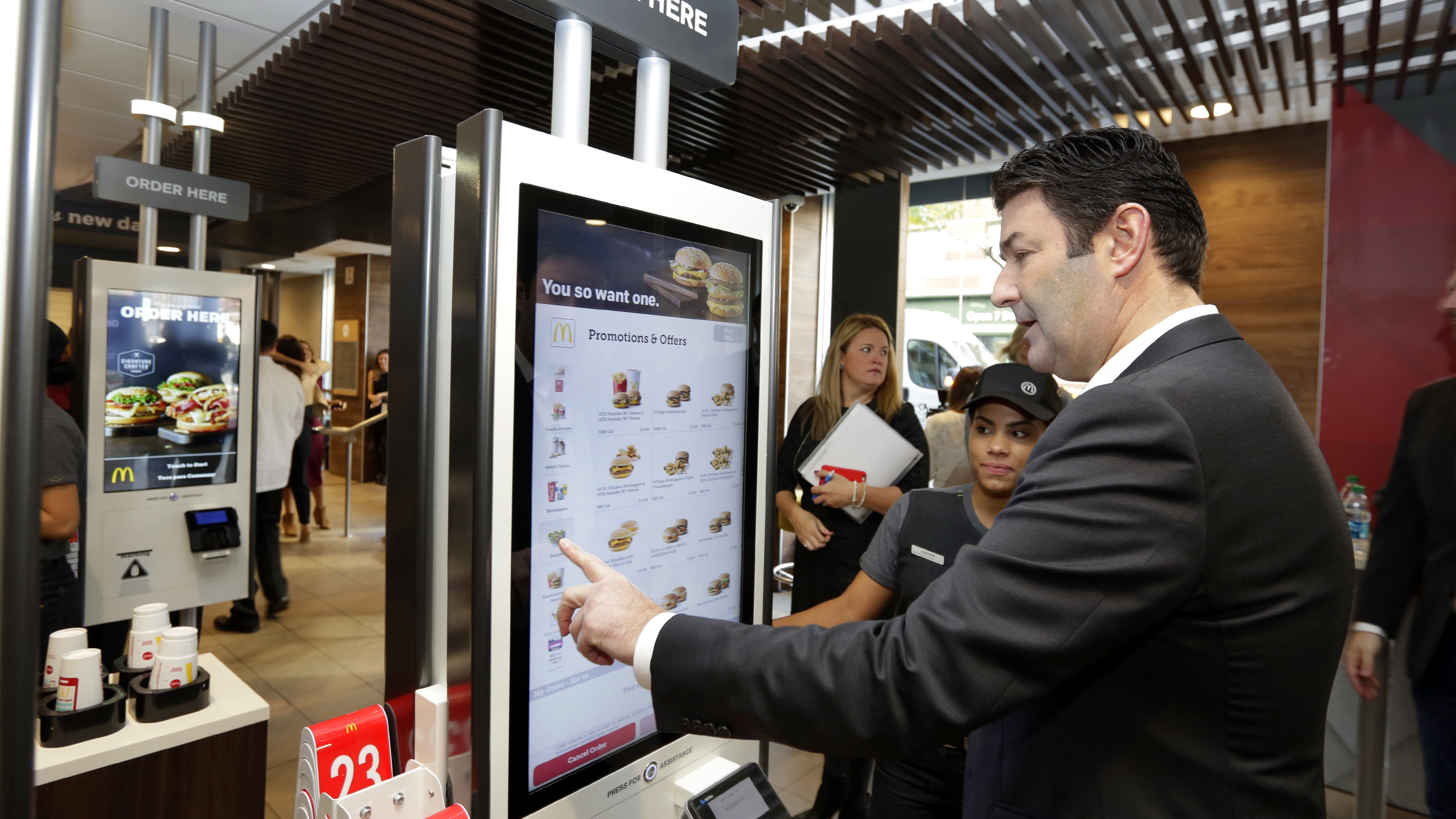 McDonald's CEO Steve Easterbrook demonstrates an order kiosk, with cashier Esmirna DeLeon, during a presentation at a McDonald's restaurant in New York's Tribeca neighborhood, Thursday, Nov. 17, 2016. On Thursday, the company said it wants to makes its fast-food outlets feel more like restaurants, with plans to eventually expand table service across its U.S. locations. (AP Photo/Richard Drew)