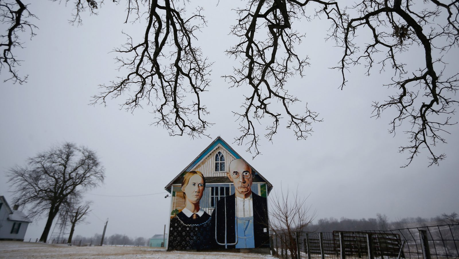 """A barn decorated with a mural inspired by Grant Wood's painting, """"American Gothic,"""" is seen in Mt. Vernon, Iowa, January 25, 2015. Artist Mark Benesh recreated the original which was painted by Grant Wood. Iowa, the American heartland. Endless farm fields and quiet towns. 56,273 square miles that are soon to become the focus of the nation as the long process of electing the next U.S. president begins. REUTERS/Jim Young TPX IMAGES OF THE DAY  PICTURE 4 OF 18 FOR WIDER IMAGE STORY 'IOWA - AMERICA'S HEARTLAND'  SEARCH 'YOUNG HEARTLAND' FOR ALL IMAGES - RTR4UNQG"""