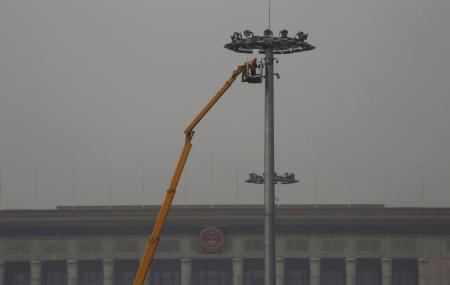 A worker maintains a street light at Tiananmen Square among smog during a polluted day in Beijing on Jan. 6, 2017.