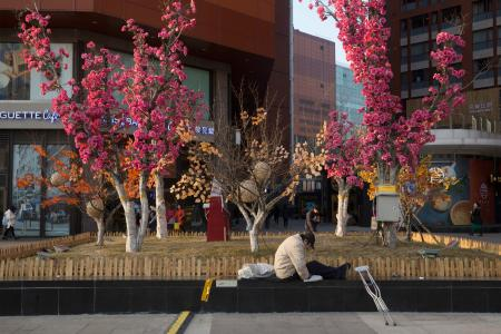 A man with crutches stretches his legs as his dog rests near him in Beijing, China, Sunday, Jan. 8, 2017. Residents enjoyed the reprieve after a weeklong smog alert as clean air returned to the Chinese capital. (AP Photo/Ng Han Guan)