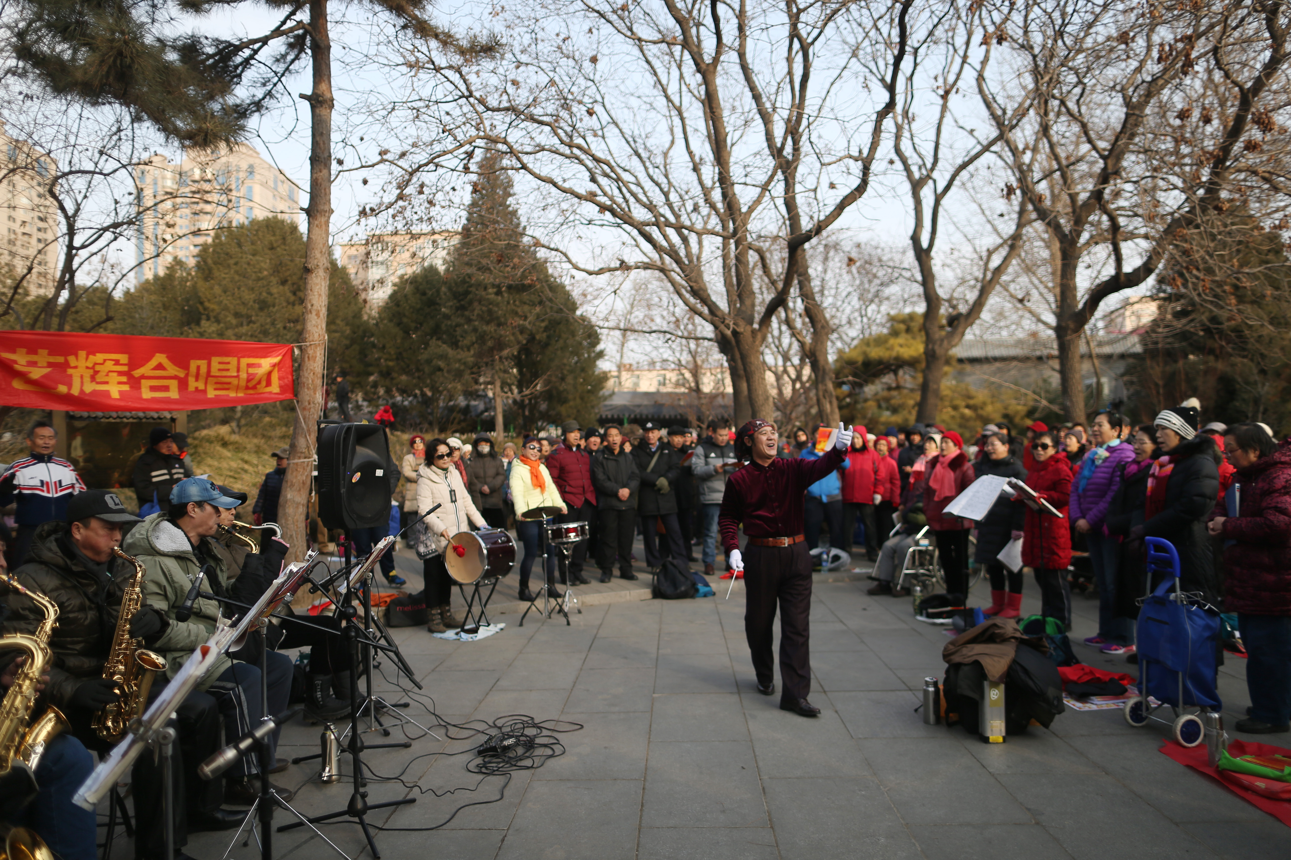A conductor leads Chinese residents of a choir singing in a park on a clear day after the end of a long orange alert for smog in Beijing, China, 08 January 2017. People came out in droves to enjoy clean air and clear skies in Beijing after the end of an orange alert for heavy air pollution which lasted seven days, beginning on 02 January 2017. EPA/HOW HWEE YOUNG