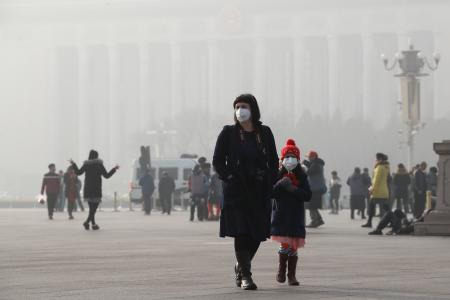 A foreign tourist and a child wearing protection masks walk through Tiananmen Square in Beijing as the capital of China is blanked by heavy smog on Wednesday, Jan. 4, 2017. China has long faced some of the worst air pollution in the world, blamed on its reliance of coal for energy and factory production, as well as a surplus of older, less efficient cars on its roads. Inadequate controls on industry and lax enforcement of standards have worsened the pollution problem. (AP Photo/Andy Wong)
