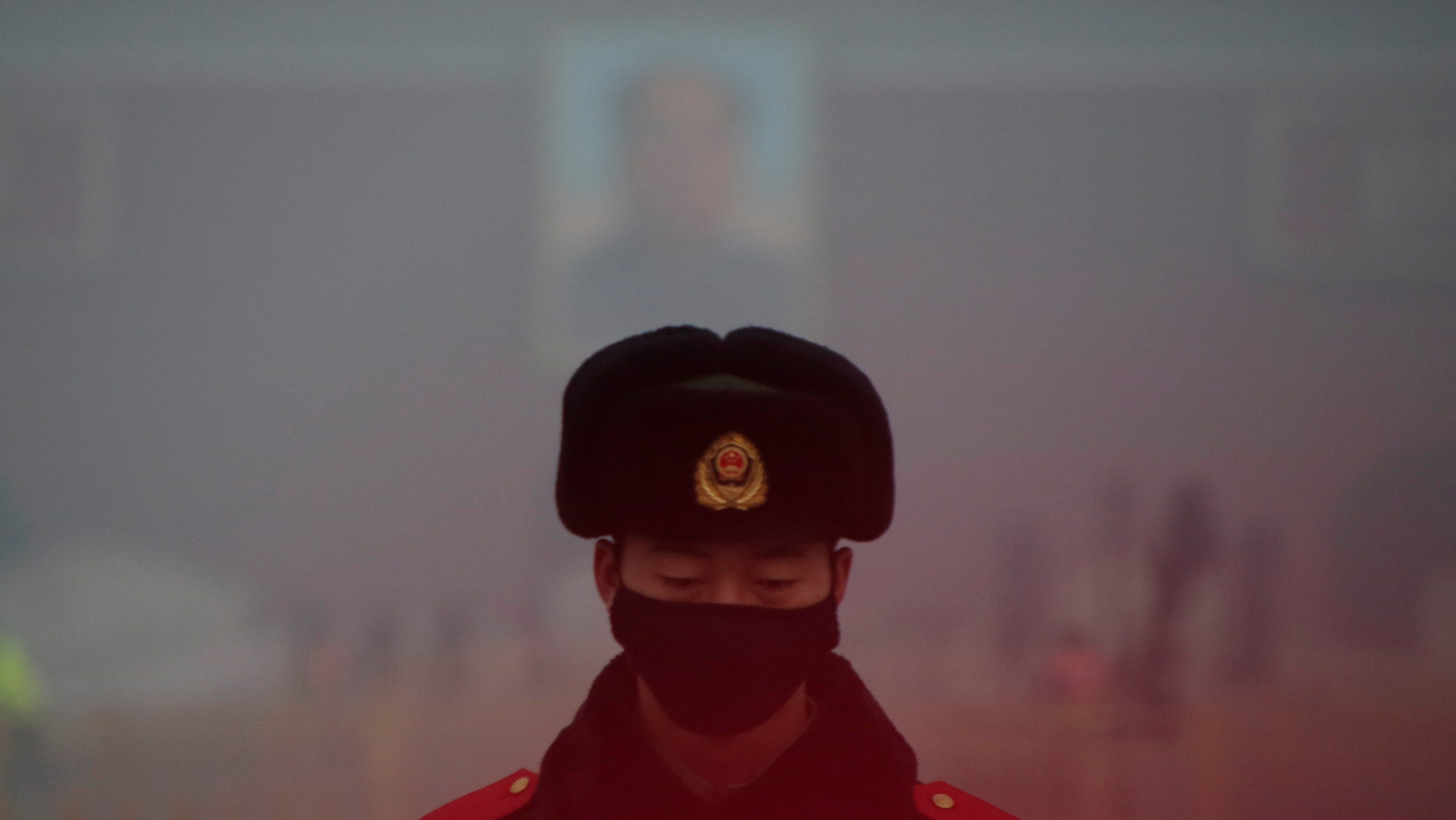 A paramilitary police officer wearing a mask stands guard in front of a portrait of the late Chairman Mao Zedong during smog at Tiananmen Square after a red alert was issued for heavy air pollution in Beijing, China, December 20, 2016. REUTERS/Jason Lee - RTX2VRON
