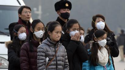 Young tourists wear masks as they stand near a Chinese Paramilitary policeman in Tiananmen Square in Beijing, China, Saturday, Dec. 19, 2015. Smog built up in the Chinese capital as the second red alert of the month went into effect, forcing many cars off the roads and restricting factory production. (AP Photo/Ng Han Guan)