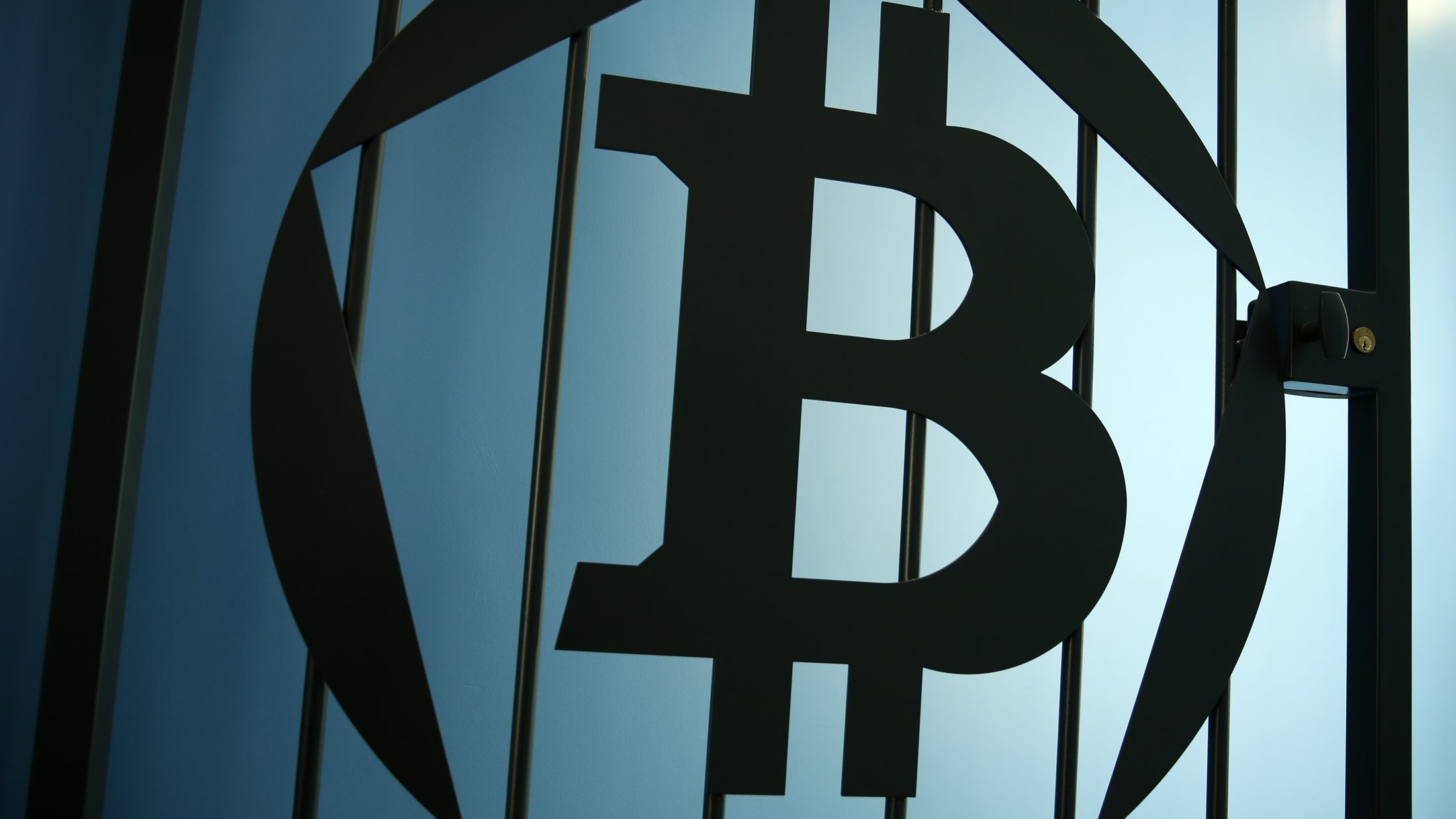 """A Bitcoin (virtual currency) logo is pictured on a door in an illustration picture taken at La Maison du Bitcoin in Paris May 27, 2015. British authorities have come out in support of digital currencies in the name of promoting financial innovation, while proposing that regulations should be drawn up to prevent their use in crime. But it is technophiles who are leading the drive to make London a real-world hub for trade in web-based """"cryptocurrencies"""", of which bitcoin is the original and still most popular.   Picture taken May 27, 2015."""