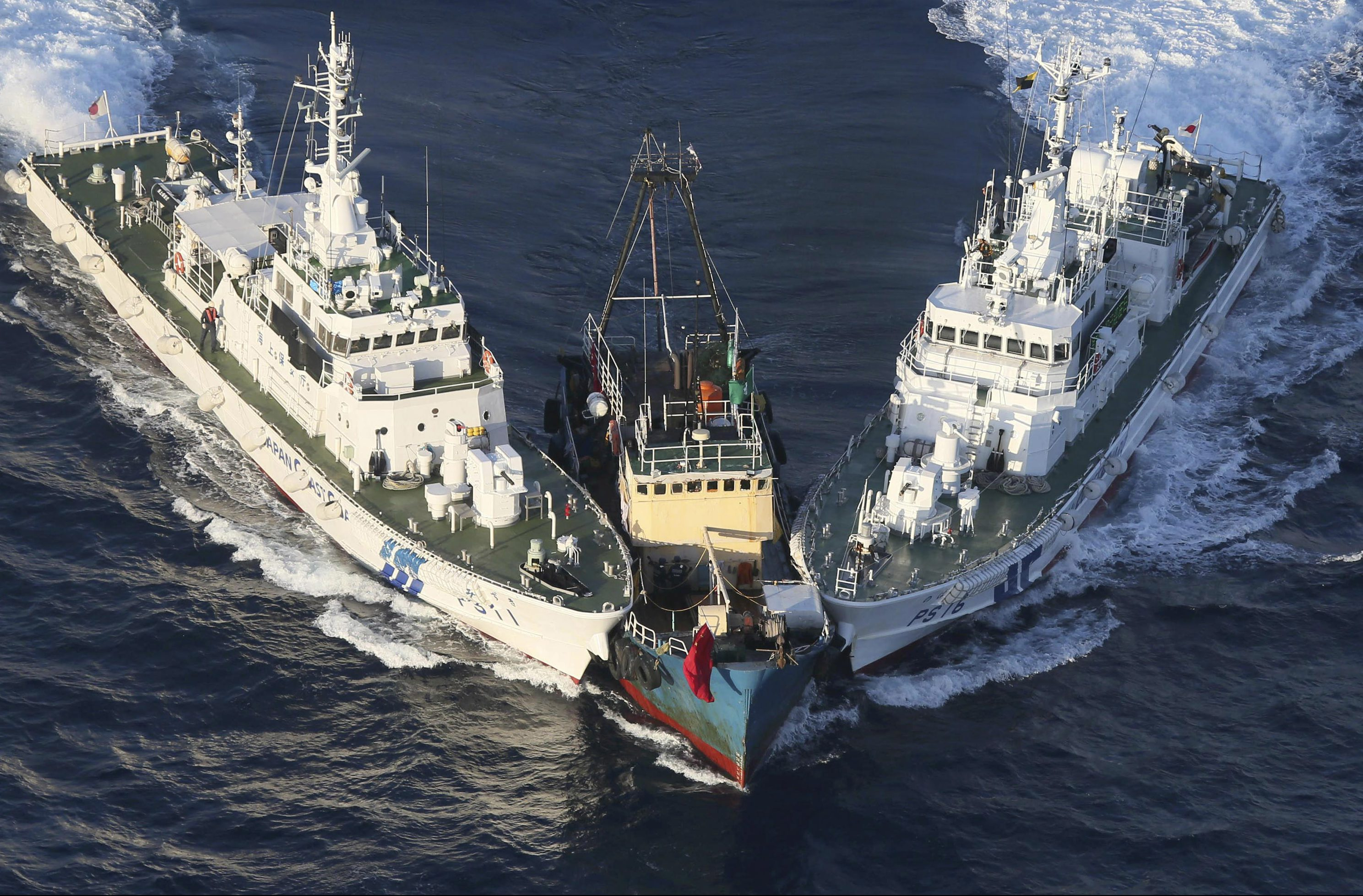 A boat, center, is surrounded by Japan Cost Guard's patrol boats after some activists descended from the boat on Uotsuri Island, one of the islands of Senkaku in Japanese and Diaoyu in Chinese, in East China Sea Wednesday, Aug. 15, 2012. Regional tensions flared on the emotional anniversary of Japan's World War II surrender as activists from China and South Korea used Wednesday's occasion to press rival territorial claims, prompting 14 arrests by Japanese authorities. The 14 people had traveled by boat from Hong Kong to the disputed islands controlled by Japan but also claimed by China and Taiwan.