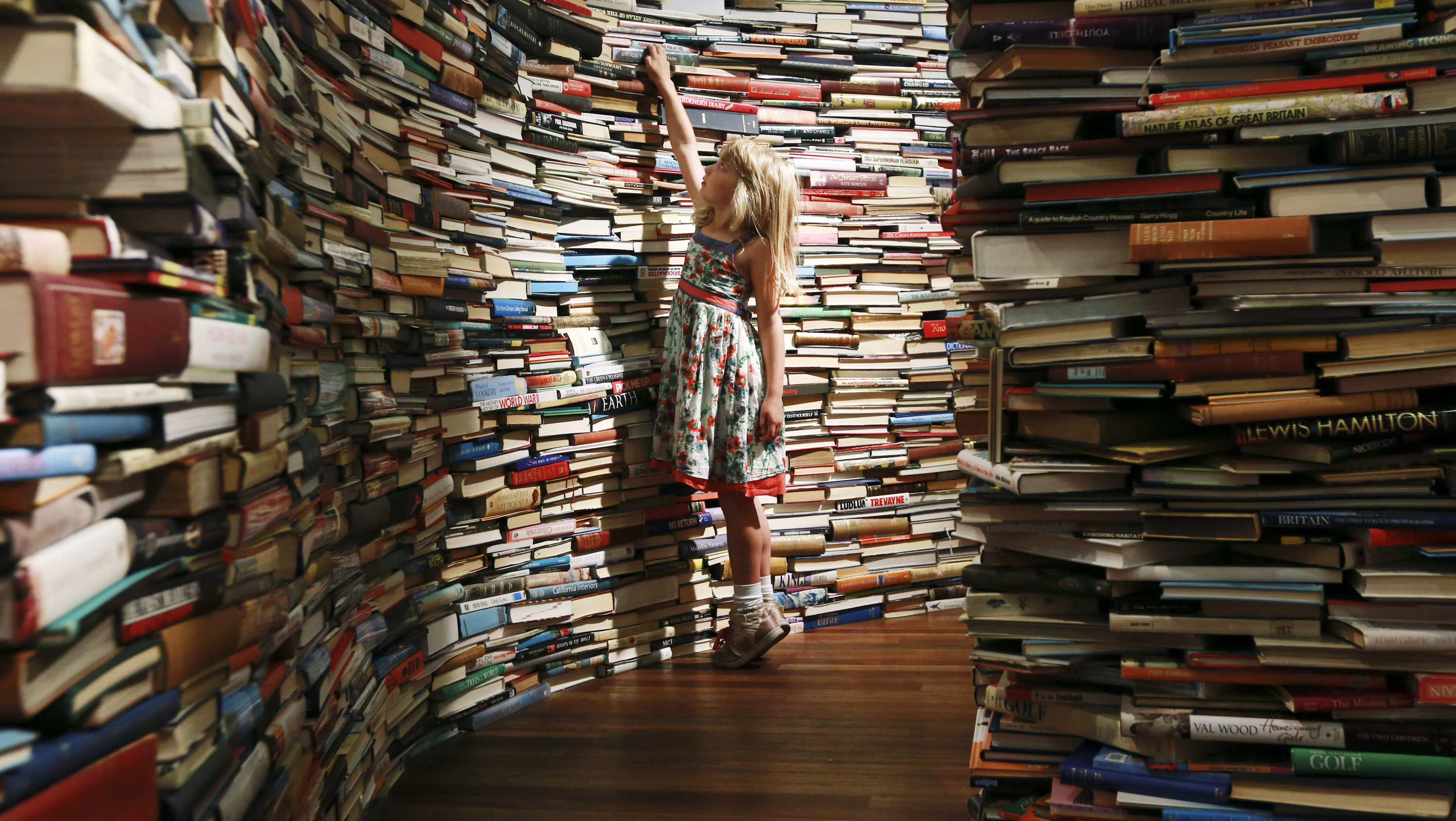 "Leona, 7, poses inside a labyrinth installation made up of 250,000 books titled ""aMAZEme"" by Marcos Saboya and Gualter Pupo at the Royal Festival Hall in central London July 31, 2012."