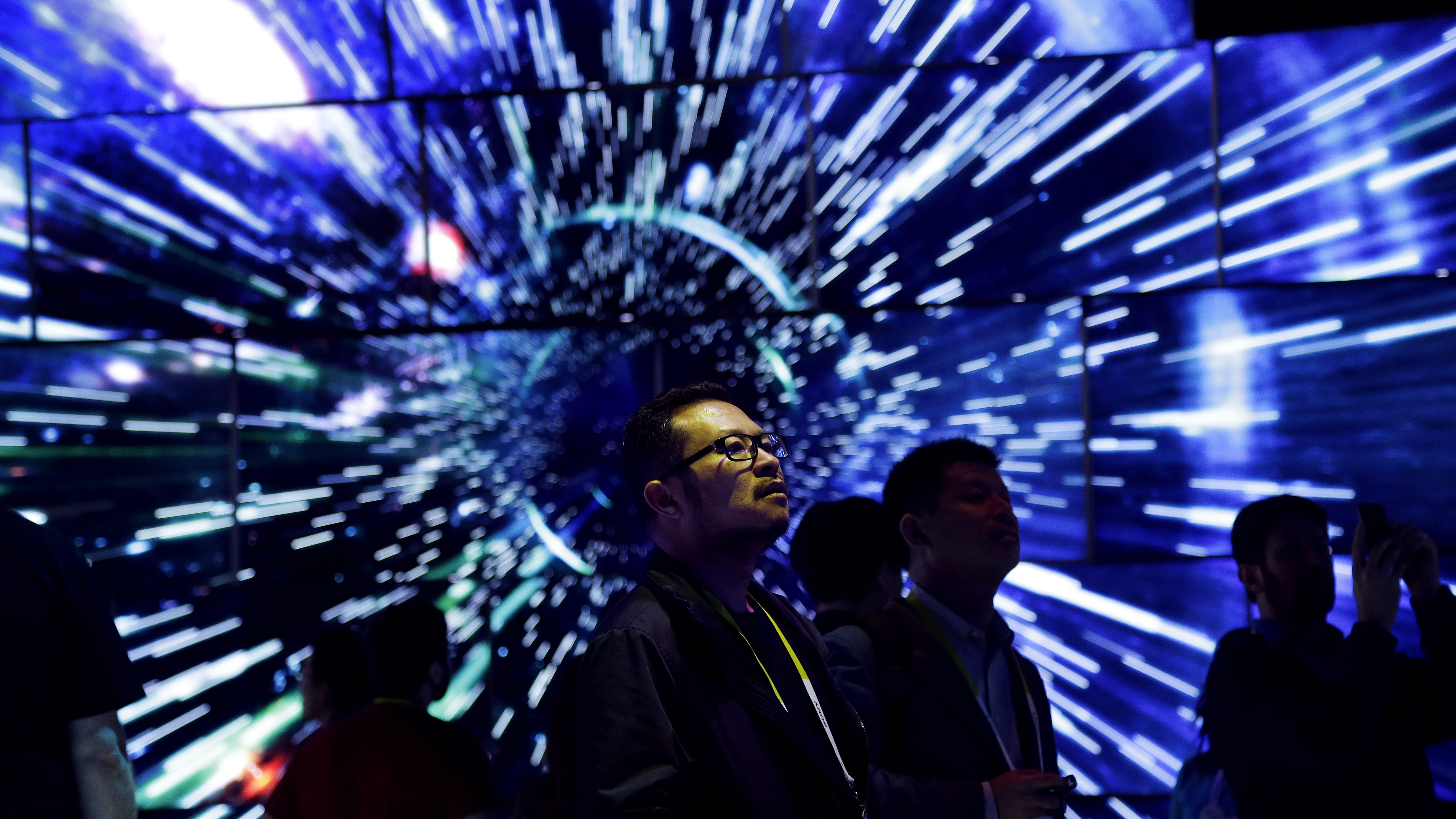 Bao Truong looks at a display of Samsung SUHD Quantum dot display TVs at the Samsung booth during CES International, Friday, Jan. 8, 2016, in Las Vegas. (AP Photo/Gregory Bull)