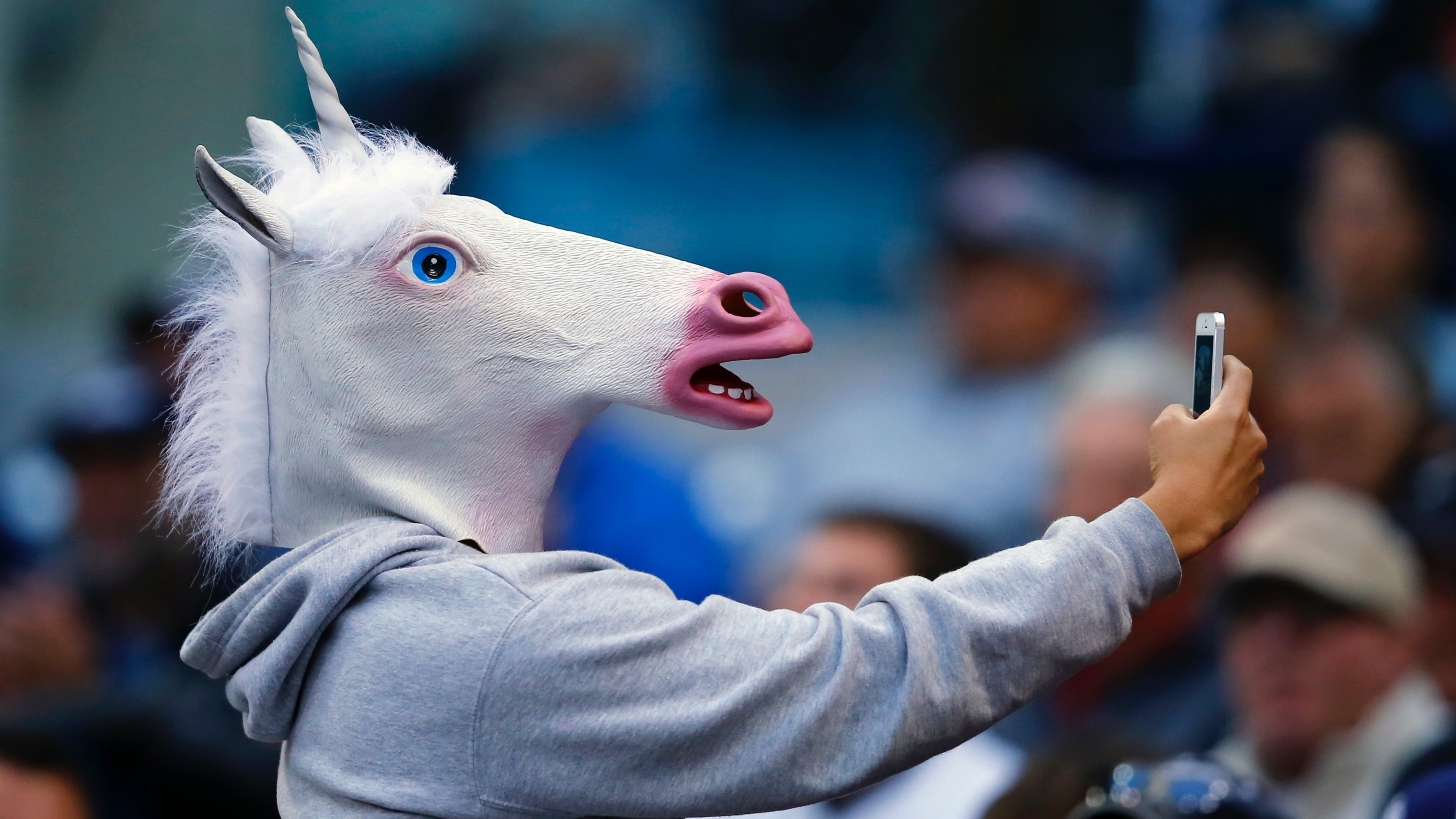 A baseball fan wearing a unicorn mask takes a picture of himself with his phone as he attends the Interleague MLB game between the San Diego Padres and the Toronto Blue Jays in San Diego, California June 2, 2013.    REUTERS/Mike Blake  (UNITED STATES - Tags: SPORT BASEBALL SOCIETY) - RTX109SM