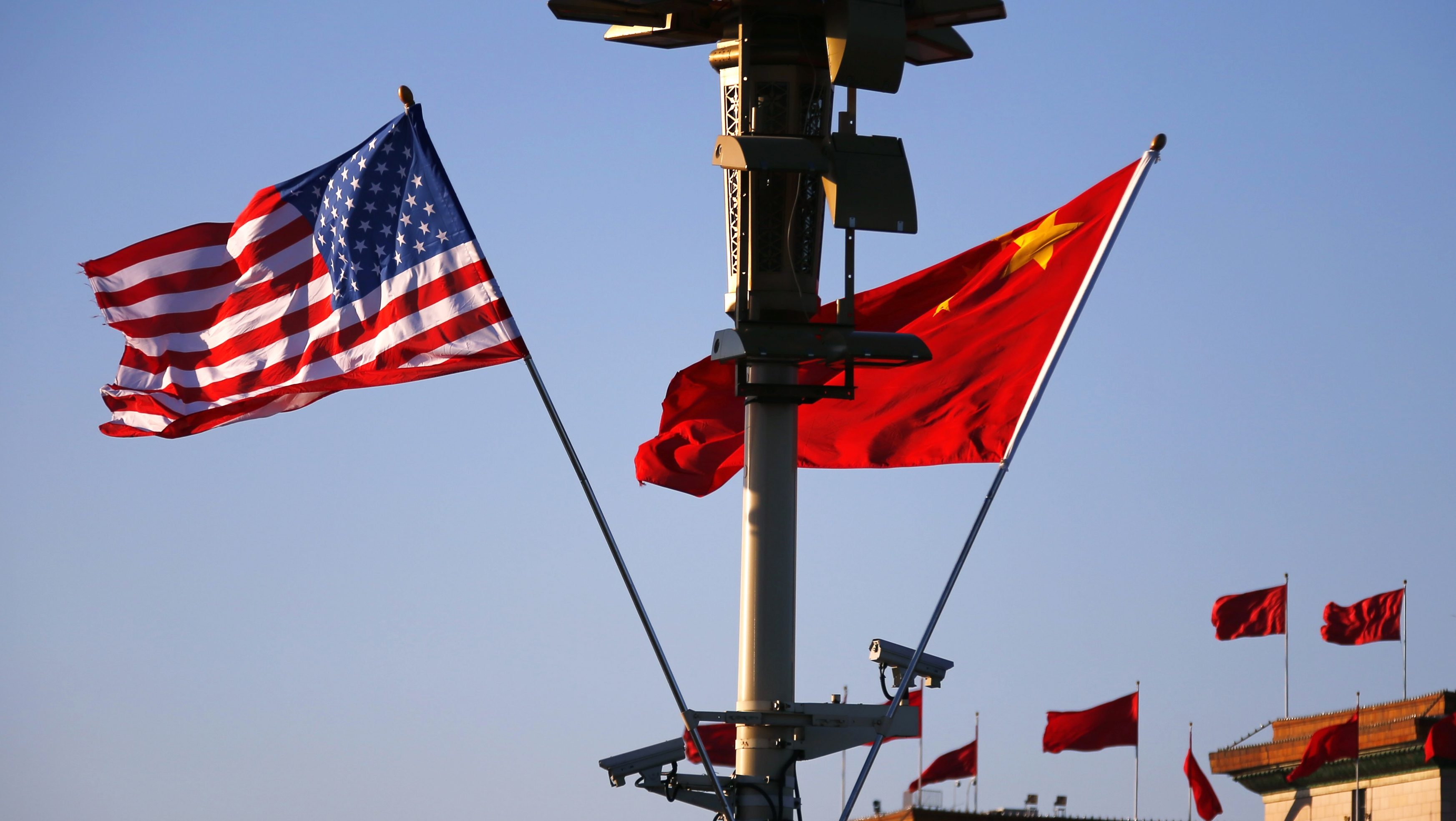 U.S. (L) and Chinese national flags flutter on a light post at the Tiananmen Square ahead of a welcoming ceremony for U.S. President Barack Obama, in Beijing, November 12, 2014. REUTERS/Petar Kujundzic (CHINA - Tags: POLITICS) - RTR4DSIF