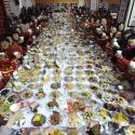 """Residents raise their glasses as they pose for photographs at a table full of dishes during a """"Ten thousand families dinner"""" organized by a local community to celebrate the upcoming Chinese Lunar New Year, in Wuhan, Hubei province January 24, 2014. A residential community in Wuhan hosted the mass dinner on Friday serving over 30,000 people with over 11,000 dishes of food cooked by the families of the community, local media reported. Picture taken January 24, 2014. REUTERS/China Daily (CHINA - Tags: FOOD ANNIVERSARY SOCIETY) CHINA OUT. NO COMMERCIAL OR EDITORIAL SALES IN CHINA - RTX17TIE"""