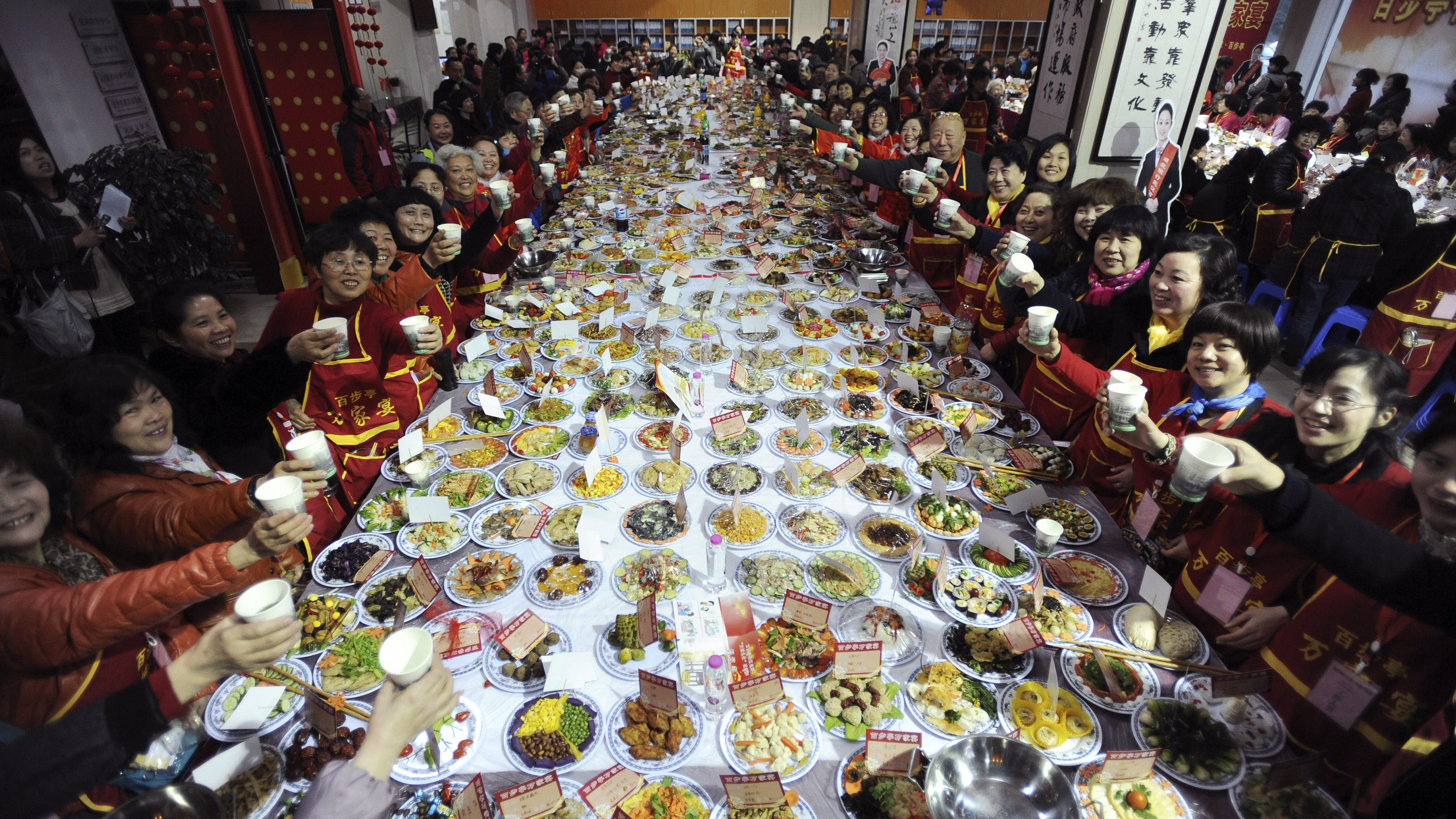 """Residents raise their glasses as they pose for photographs at a table full of dishes during a """"Ten thousand families dinner"""" organized by a local community to celebrate the upcoming Chinese Lunar New Year, in Wuhan, Hubei province January 24, 2014. A residential community in Wuhan hosted the mass dinner on Friday serving over 30,000 people with over 11,000 dishes of food cooked by the families of the community, local media reported. Picture taken January 24, 2014.  REUTERS/China Daily"""