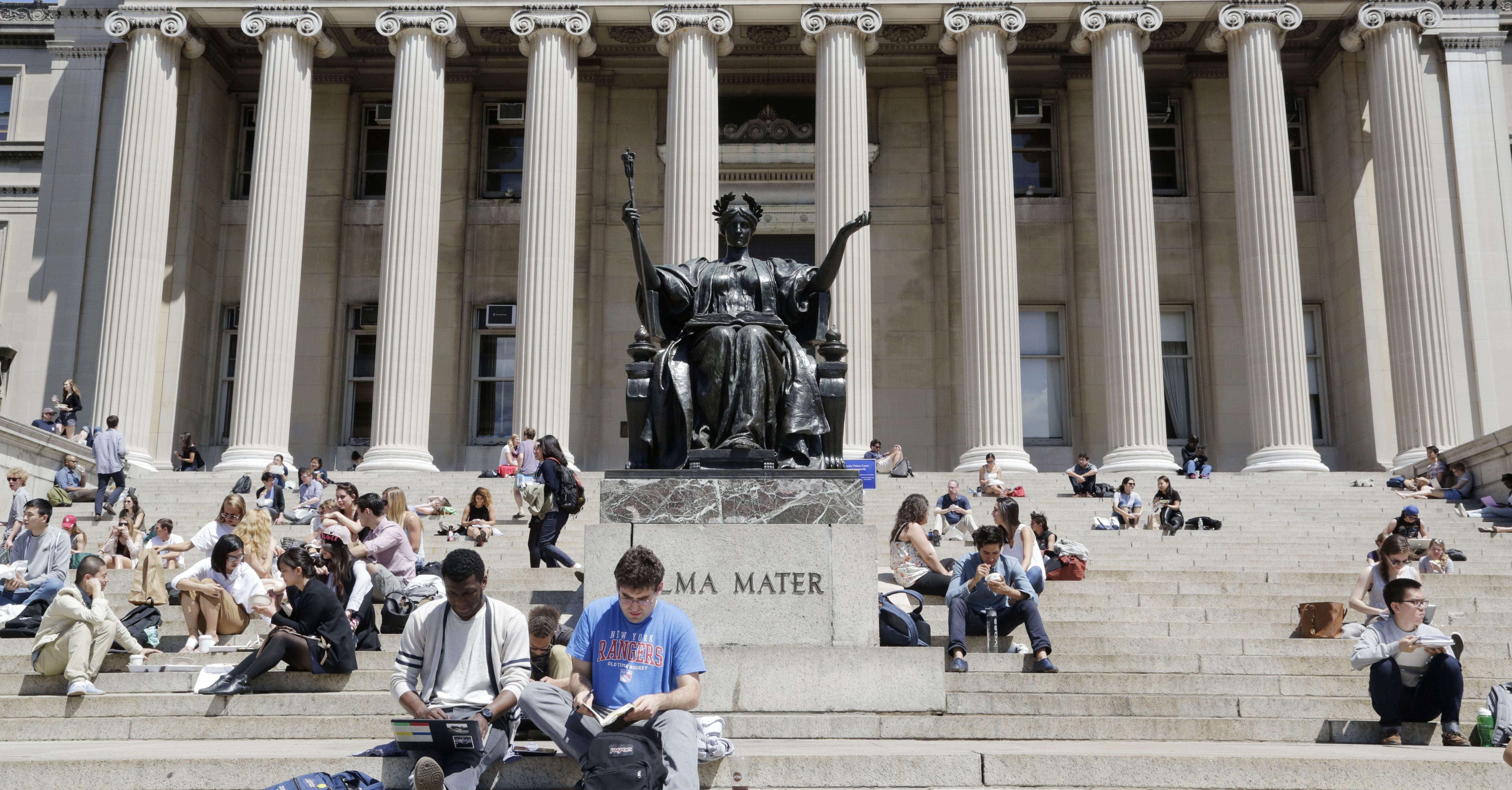 Students sunbathe on the steps of Columbia University's Low Memorial Library next to Daniel Chester French's sculpture, Alma Mater, April 29, 2015 in New York.