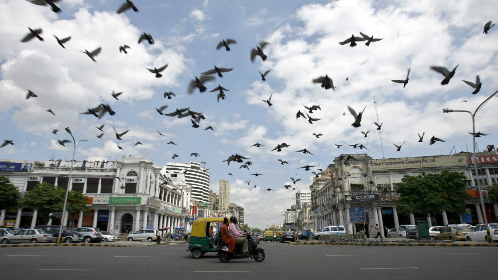 Pigeons fly as clouds gather over New Delhi's Connaught Place July 16, 2009. India's monsoon rains were six percent above normal in the week to July 15, rebounding after a prolonged weak patch, the weather office said on Thursday.