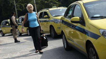 A passenger walks near taxis parked on the access of the Santos Dumont airport during a protest against the online car-sharing service Uber in Rio de Janeiro, Brazil