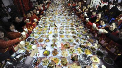 A massive table with food and 20 or so guests down each side raising their glasses.