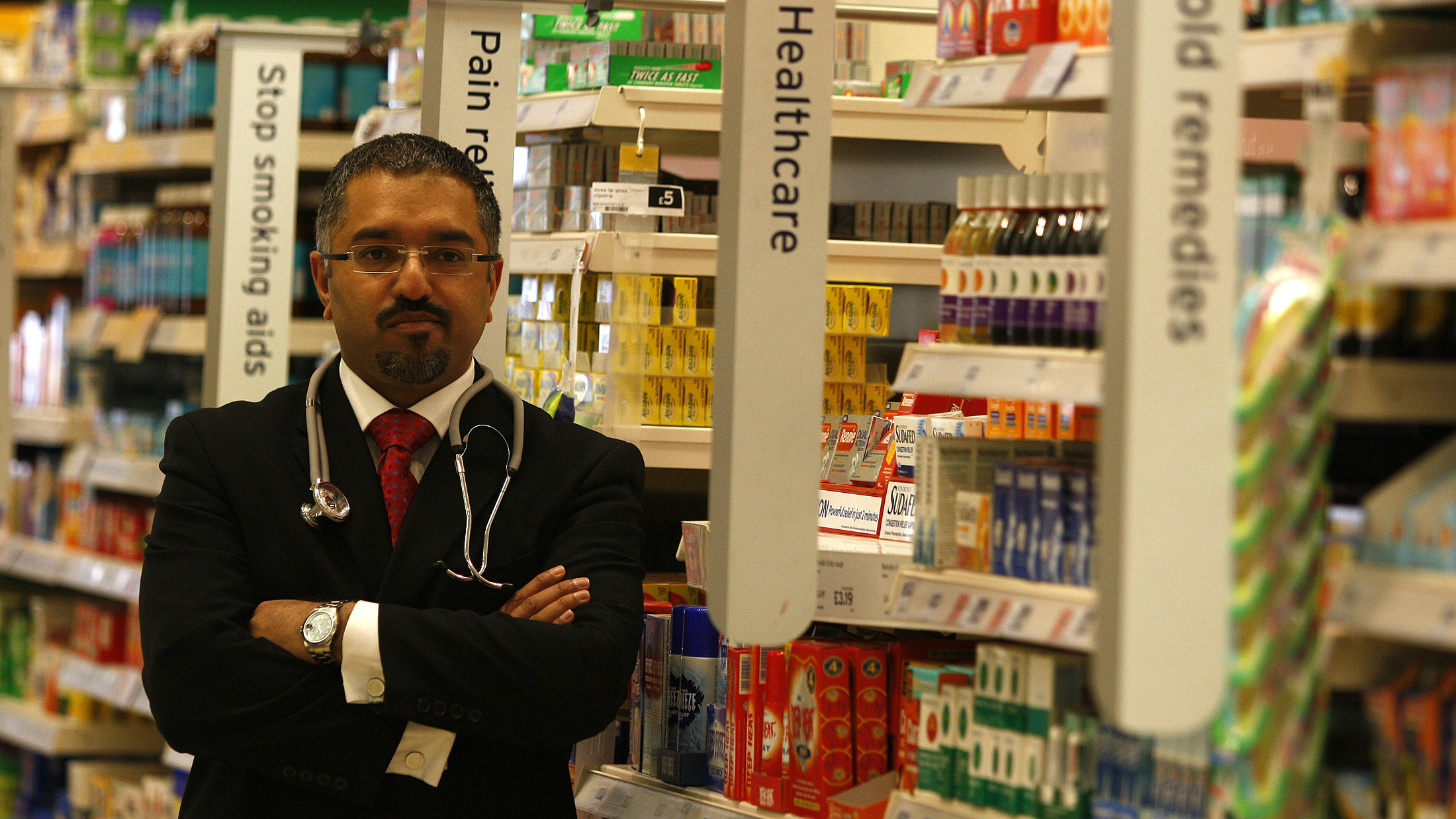 Doctor Mohammed Jiva poses for photographers in the medicine aisle inside the Sainsbury's store in Heaton Park, Manchester, northern England, March 3, 2008. The supermarket began an out-of-hours GP appointment scheme, and local media reported that the supermarket was the first in the country to offer GP appointments. REUTERS/Phil Noble (BRITAIN)