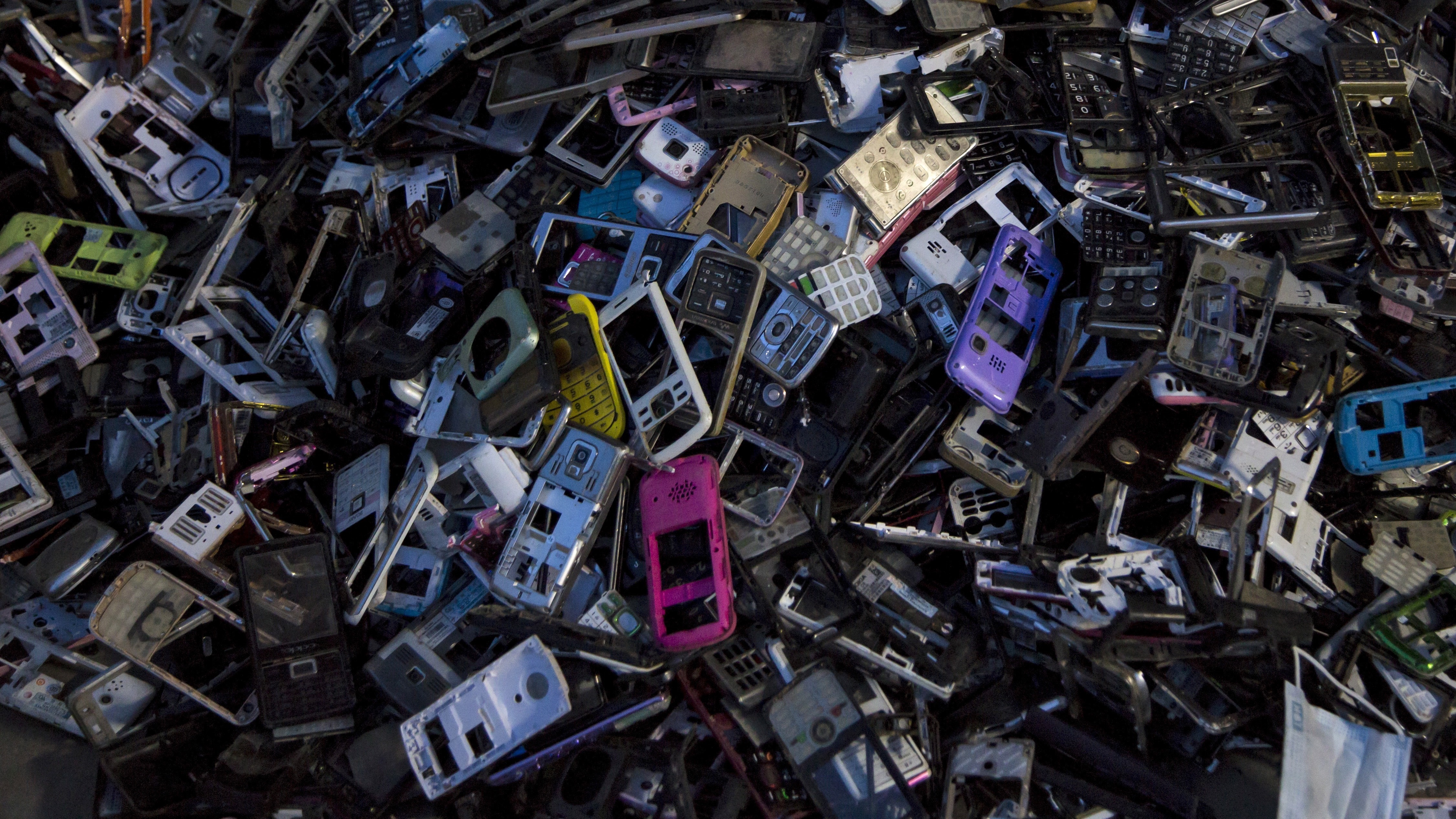 """Old cellular phone components are discarded inside a workshop in the township of Guiyu in China's southern Guangdong province June 10, 2015. The town of Guiyu in the economic powerhouse of Guangdong province in China has long been known as one of the worldís largest electronic waste dump sites. At its peak, some 5,000 workshops in the village recycle 15,000 tonnes of waste daily including hard drives, mobile phones, computer screens and computers shipped in from across the world. Many of the workers, however, work in poorly ventilated workshops with little protective gear, prying open discarded electronics with their bare hands. Plastic circuit boards are also melted down to salvage bits of valuable metals such as gold, copper and aluminum. As a result, large amounts of pollutants, heavy metals and chemicals are released into the rivers nearby, severely contaminating local water supplies, devastating farm harvests and damaging the health of residents. The stench of burnt plastic envelops the small town of Guiyu, while some rivers are black with industrial effluent. According to research conducted by Southern Chinaís Shantou University, Guiyuís air and water is heavily contaminated by toxic metal particles. As a result, children living there have abnormally high levels of lead in their blood, the study found. While most of the e-waste was once imported into China and processed in Guiyu, much more of the discarded e-waste now comes from within China as the country grows in affluence. China now produces 6.1 million metric tonnes of e-waste a year, according to the Ministry of Industry and Information Technology, second only to the U.S with 7.2 million tonnes. REUTERS/Tyrone Siu   PICTURE 12 OF 18 FOR WIDER IMAGE STORY """"WORLD'S LARGEST ELECTRONIC WASTE DUMP"""" SEARCH """"GUIYU SIU"""" FOR ALL IMAGES   - RTX1IUQV"""
