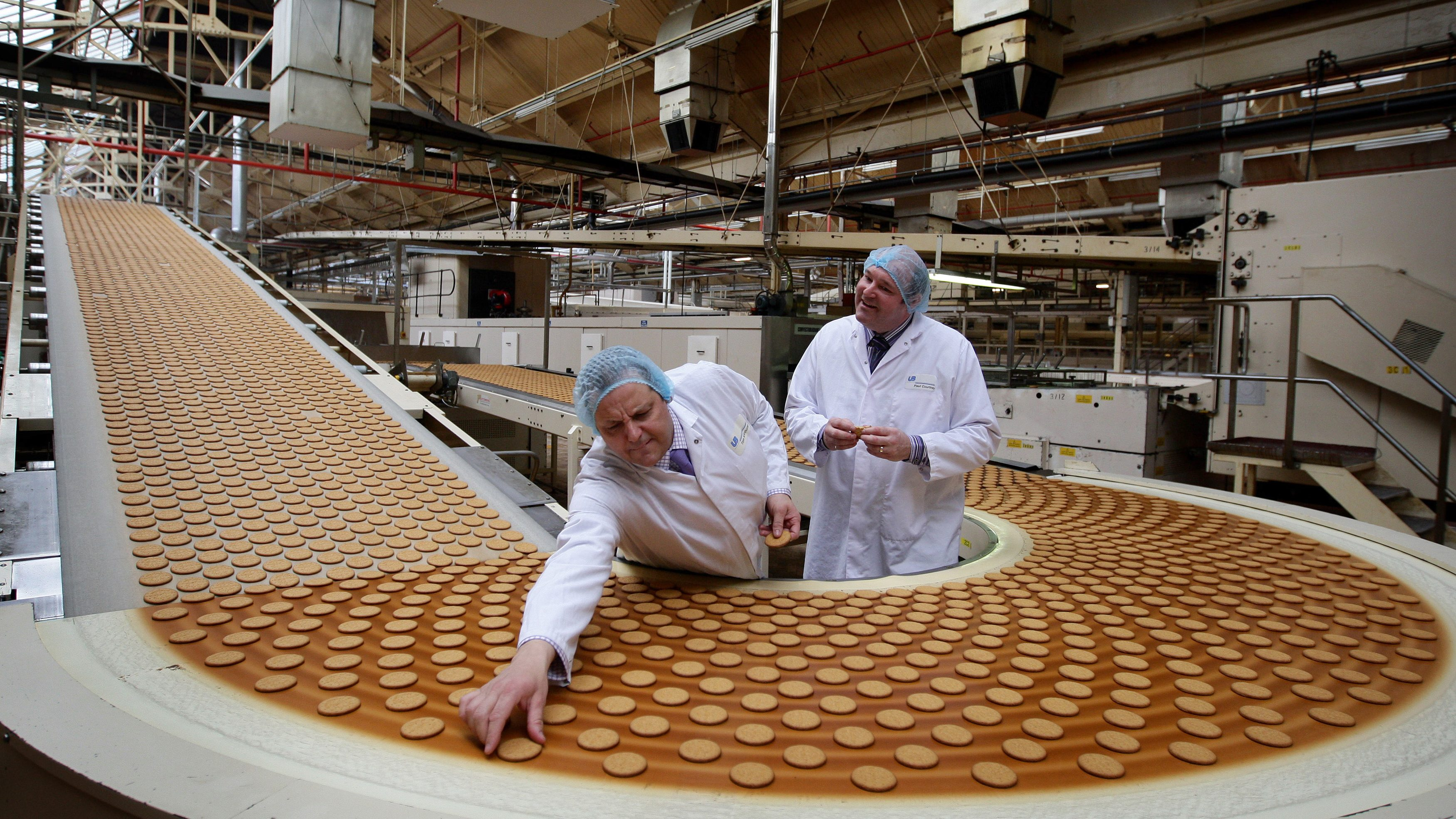 Design and Development Head Chef , Paul Courtney (R) and Manufacturing Manager, Tom Kilcourse, pose for a photograph on a biscuit production line at the McVitie's factory in Stockport, northern England March 25, 2011. Britain's Prince William has asked the company to produce a chocolate biscuit cake, as an addition to the official wedding cake to be made by Fiona Cairns, for his wedding to Kate Middleton on April 29.   Photograph taken on March 25, 2011.