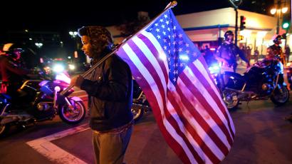 US flag carried by man in CA protest.
